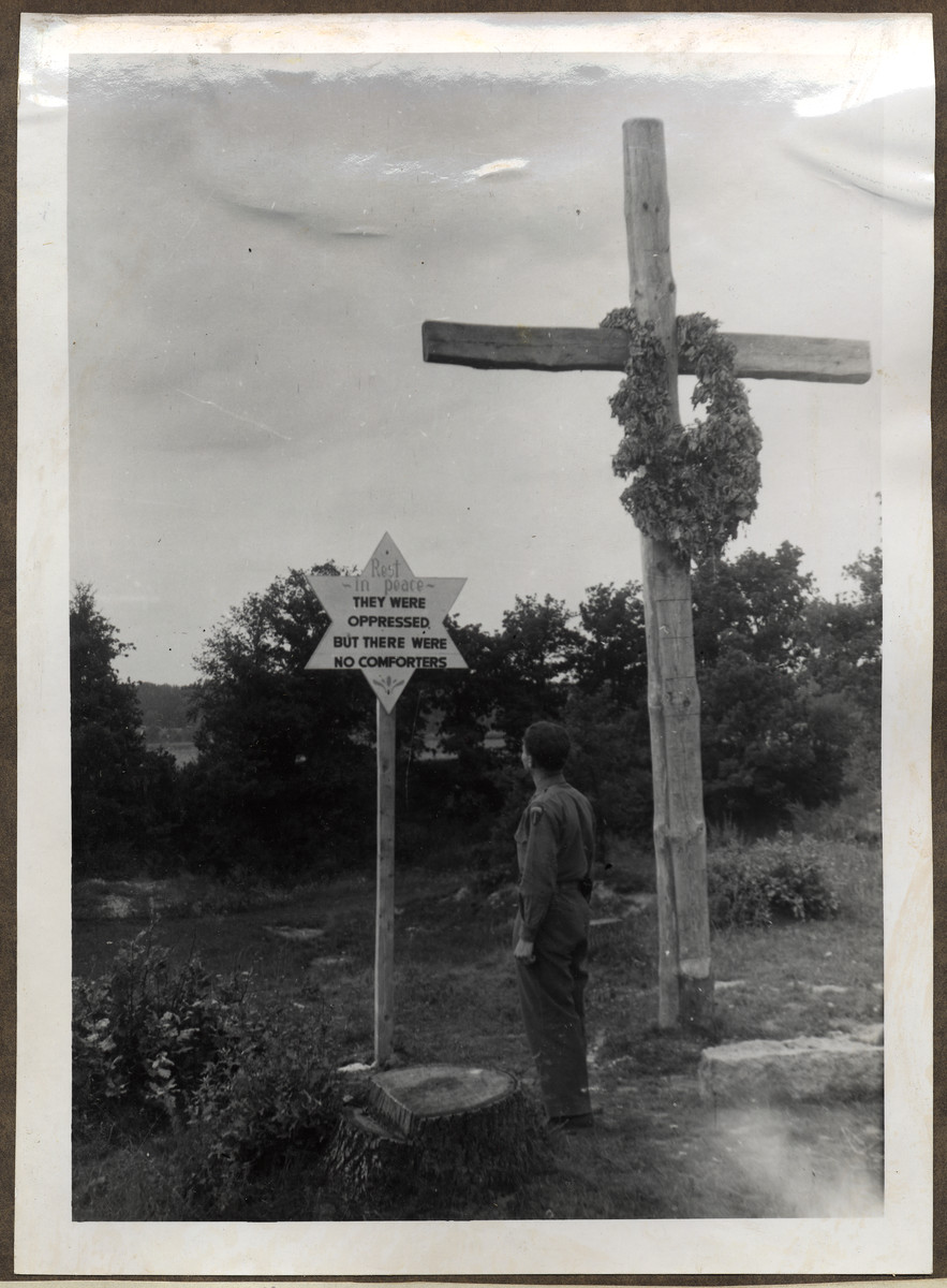 """An American soldier studies a grave marker on the sight of a mass grave of death march victims.  The original caption reads: """"A mass grave of Concentration Camp inmates murdered as the SS was chasing them along the roads, away from the persuing Americans - when liberation was so near""""."""