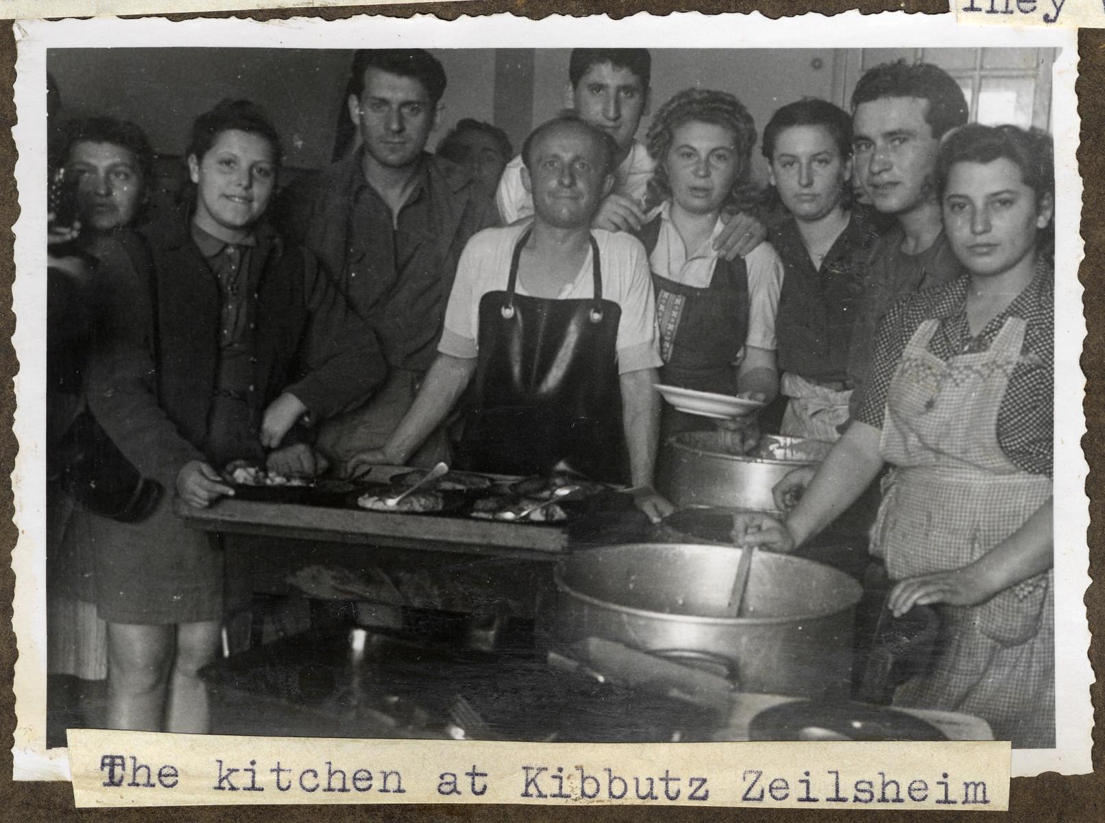 Jewish displaced persons gather around the stove in the kitchen in Kibbutz Zeilsheim