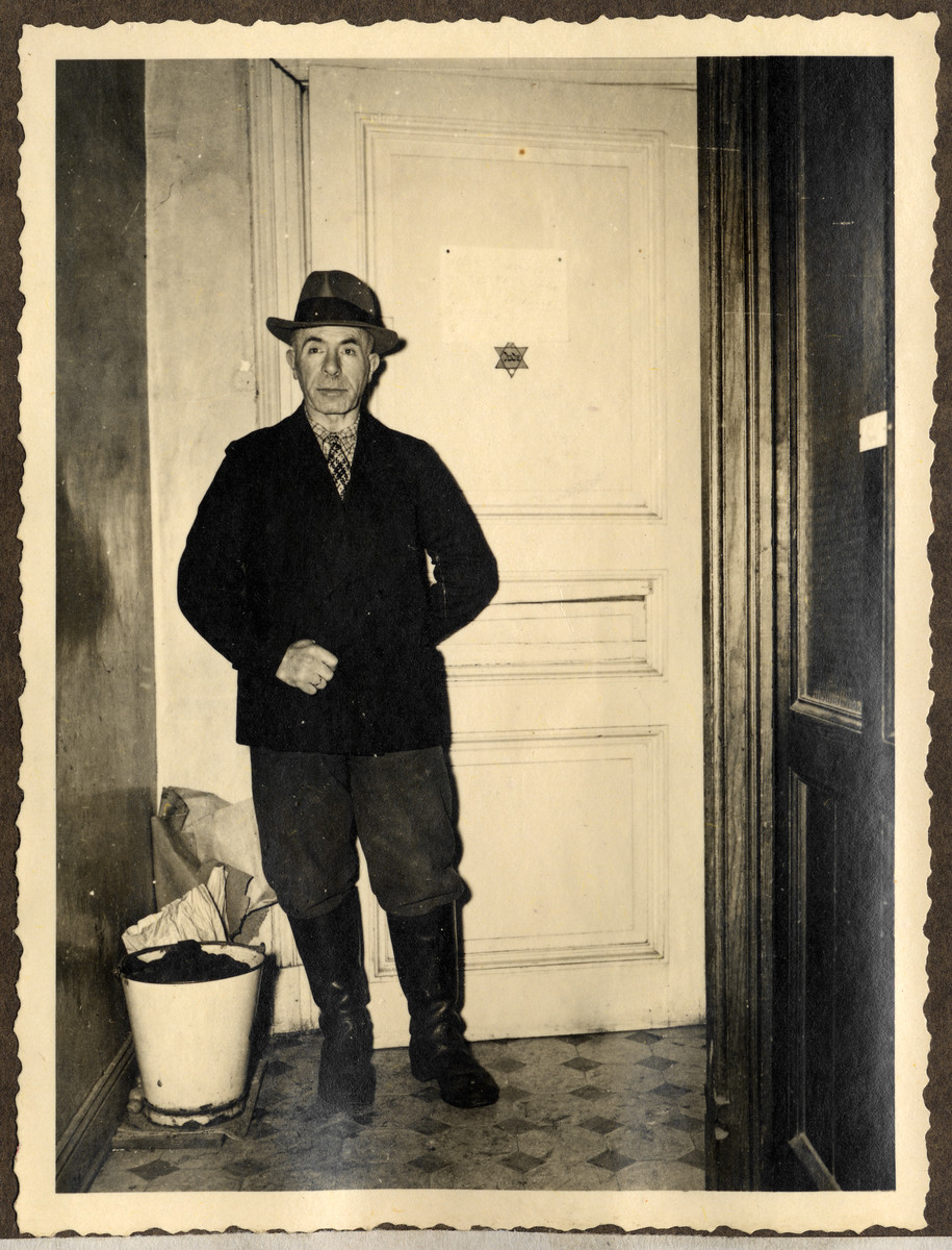 Mr. Lowenthal, the first Jew liberated in Germany, stands in the entrance to his home in Aachen; a Jewish star bedecks the door.