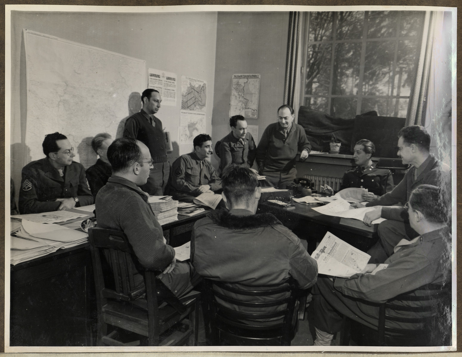 Members of the American Communications Unit responsible for writing newspapers for distribution in Germany meet for an editorial conference in The Habe Circus in Luxembourg.  Joseph Eaton is pictured in profile on the far right.