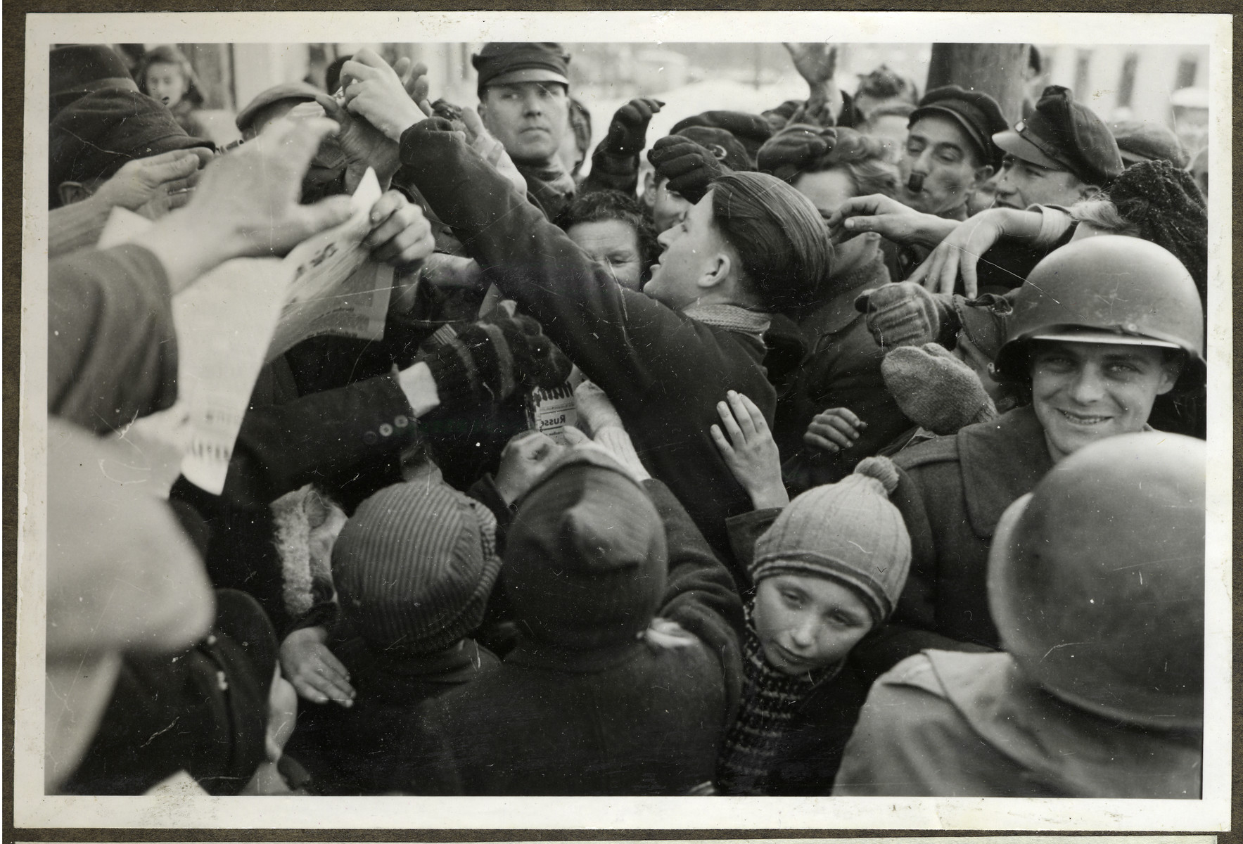 People of Ihn fight for a copy of the Mitteilungen, weekly newspaper of the 12th Army Group delivered to them.  Joseph Eaton is pictured facing the camera on the right.