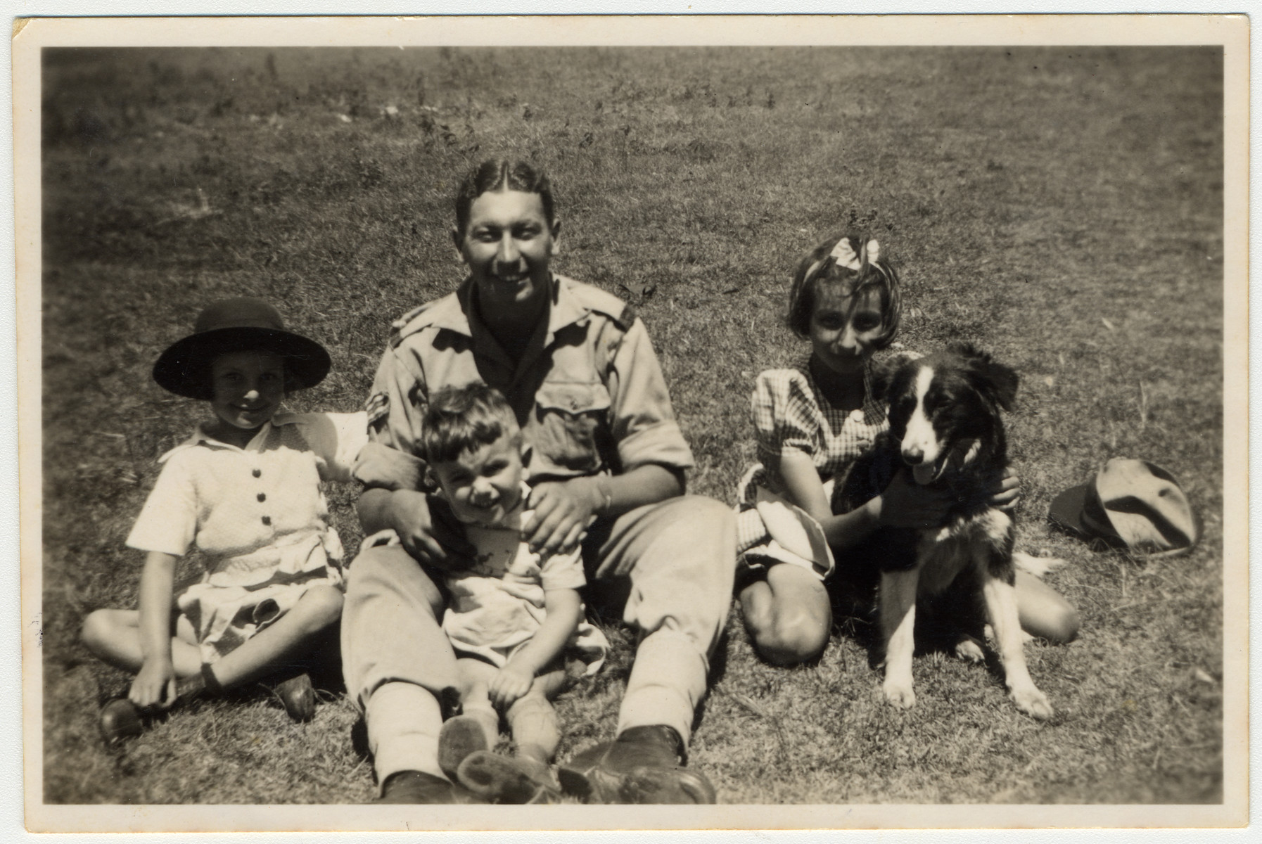A Jewish soldier in the British army poses with refugee children from Germany on their farm in Kenya where he had come to celebrate Jewish holidays.  Gisela Berg is on the far left and her sister Inge is on the right.  In the center is a Jewish British soldier and Egon Berg.