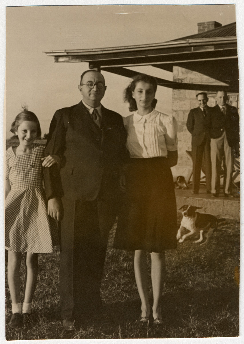 A German-Jewish refugee poses with his two daughters before the celebration of Passover.  Pictured are Gisela, Joseph and Inge Berg.  In background are Adolf Baum and Mr. Tillingham, who came to the farm for Jewish religious services.