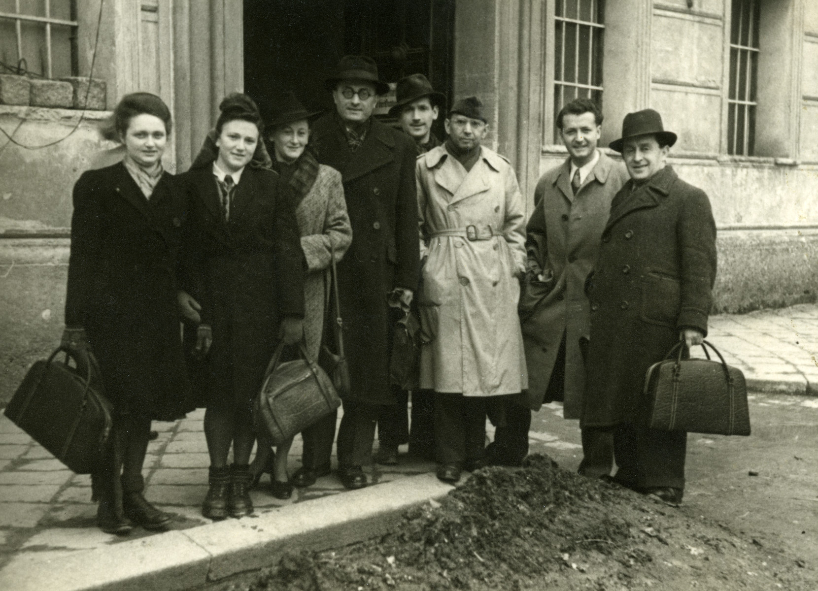 Group portrait of displaced persons and HIAS personnel in Salzburg, Austria.  Esther Wagner is standing second from the left.  Dr. Kenneth Eugene Goodwin, head of the HIAS office is third from the right in a raincoat.