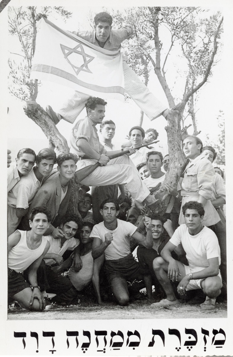 """Group portrait of teenagers in Mahane David, an immigration camp for North African Jews en route to Israel, holding an Israeli flag and rifle.  The original caption reads: """" A remembrance from Mahane David."""""""
