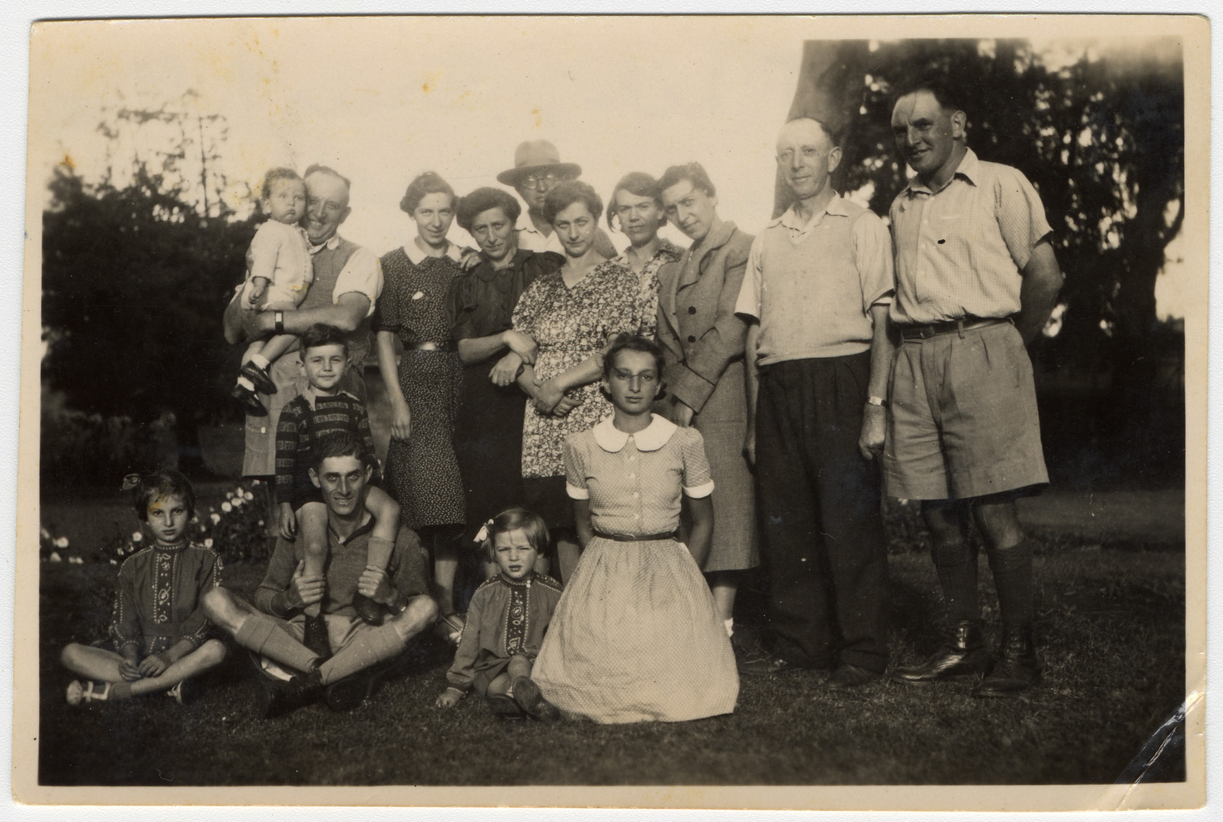 Group portrait of an extended German Jewish family who had found refuge in Kenya.  First row, left to right: Gisela Berg, Herman Mayer with Igon on his shoulders, Hannah, and Inge Berg.  Second row, left to right: Ernest Berg holding Phillip, Else Berg, Klara Berg, Joseph Berg, Erna Berg, Rosel Berg, Sara Berg, Josef, and Adolf.