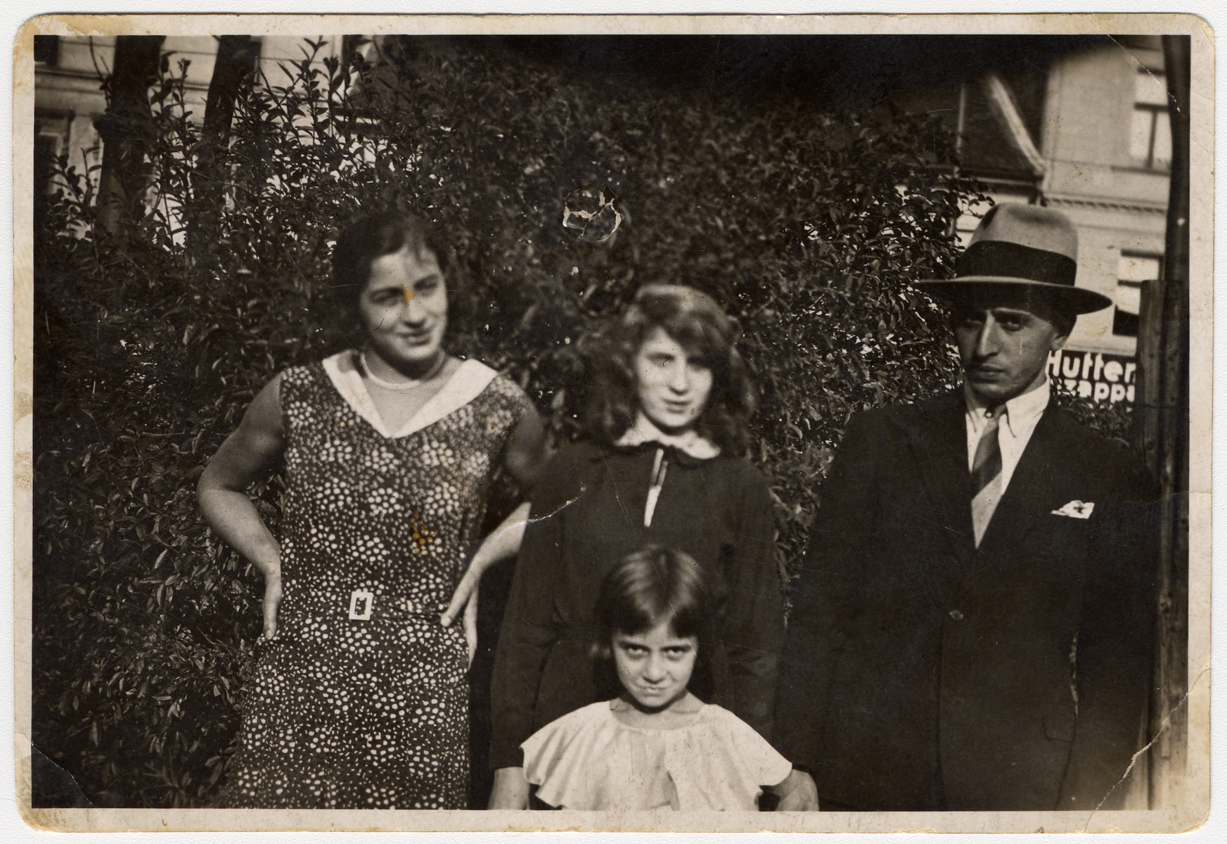A family poses outside on a city street in Budapest.  Pictured are Anges Biel's mother's (Katalin) family. From left to right are siblings Gizi, Teri, and Jeno. The little girl on the bottom row is Ibolya.