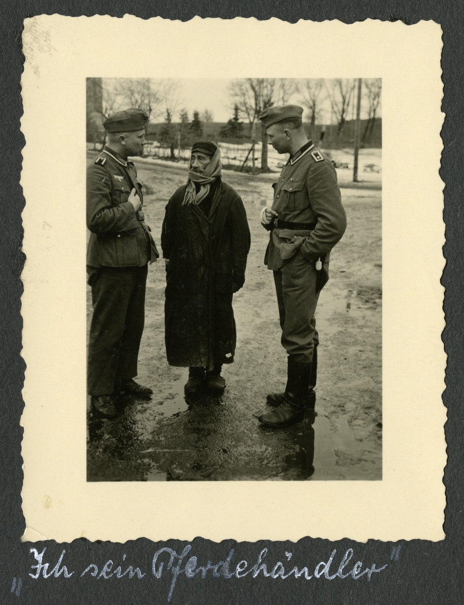 "Two German soldiers interrogate a bearded Polish Jew.  The original caption [quotation marks in original] reads: ""I am a horse-trader."""