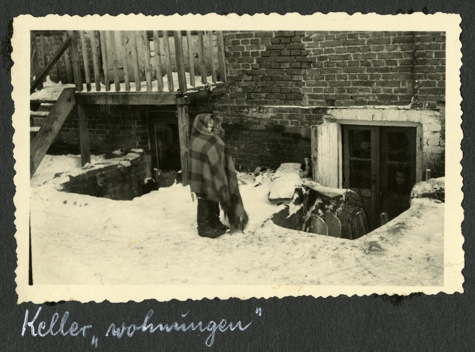 """A Polish Jew wrapped in a blanket stands in the snow outside a basement apartmnet.  The original caption reads [quotation marks in original]: Basement """"living quarters."""""""