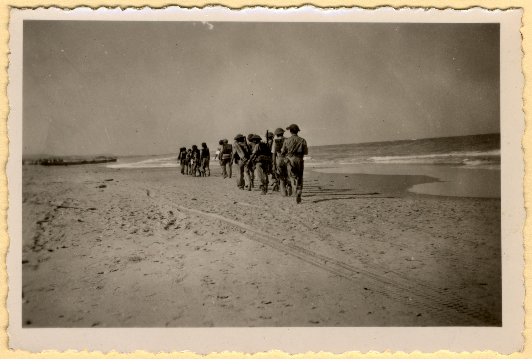 A column of Israeli soldiers marches down the beach during a demolition raid practice.
