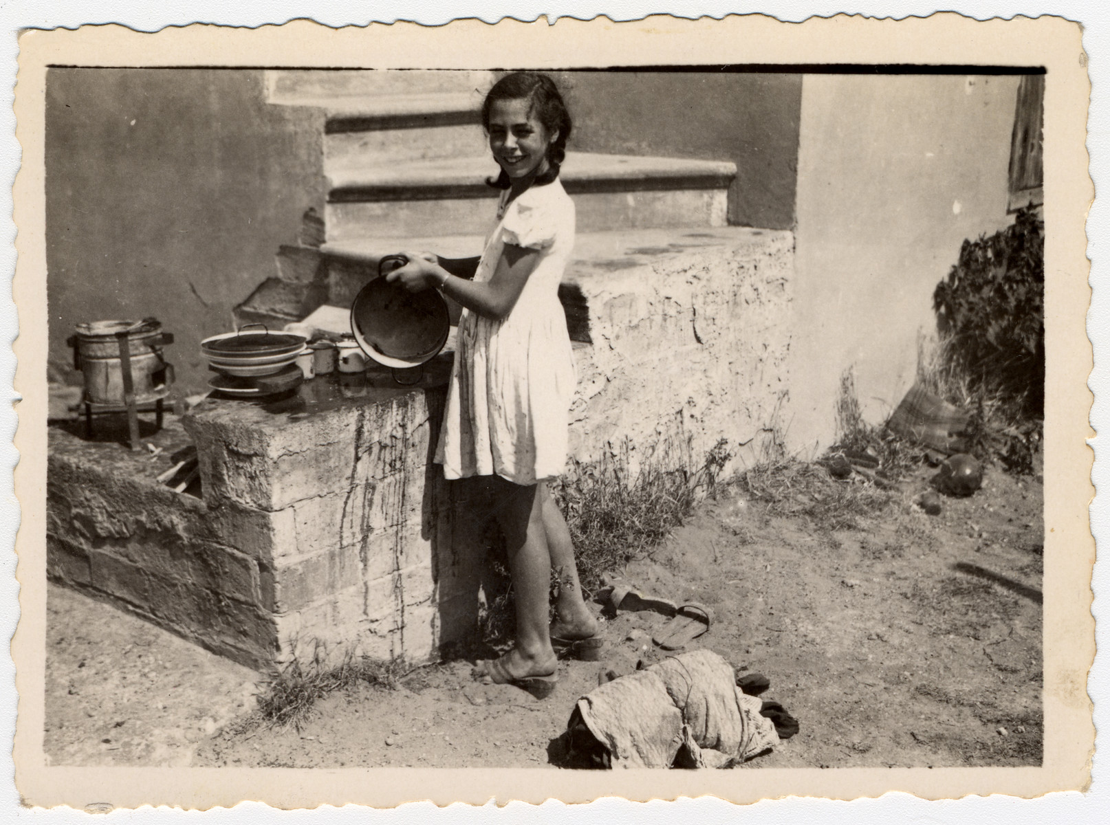 A German-Jewish refugee girl washes dishes outdoors in Shkoset Albania.  Pictured is Johanna Jutta Gerechter.