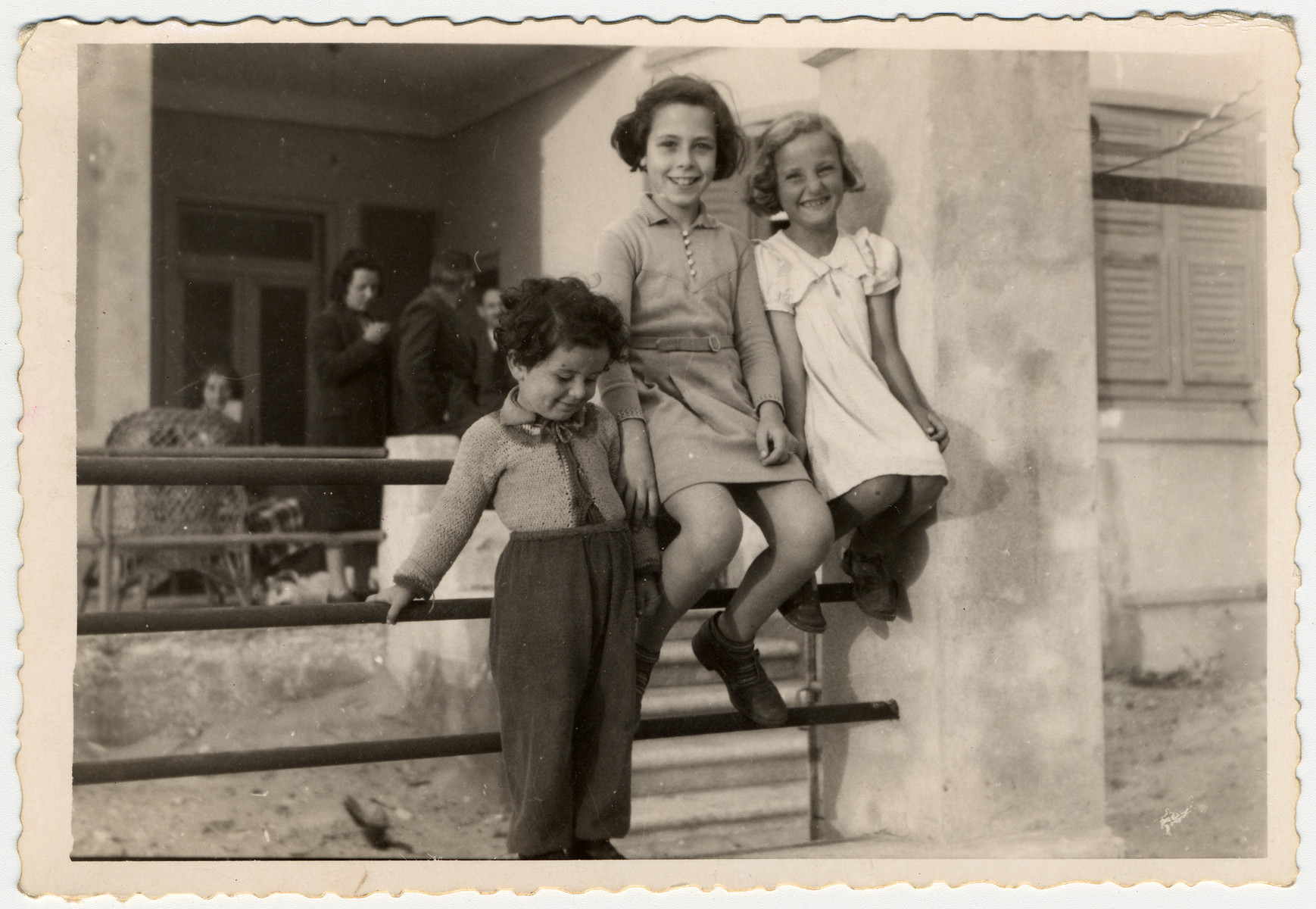 Three German or Austrian Jewish children living in Albania as refugees sit on the railing of a home.  Pictured in the center is Johanna Gerechter.  Seated to her right is Trude Kraus.  The woman on the left behind the chair is Finny Mandel and the man on the right is Hans Krahl.