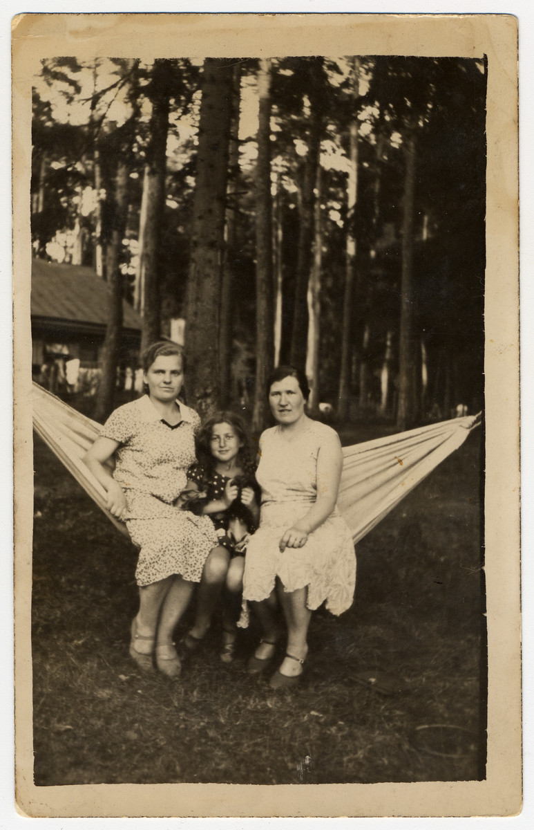 A Lithuanian Jewish woman and her daughter sit together on a hammock with their Lithuanian housekeeper.  Pictured from left to right are Franute Grunskaite, Sara Ginaite and Rebecca Giniene.  Franute Grunskaite was later recognized by Yad Vashem as Righteous Among the Nations for saving Sara's cousin, Tania Viroviciene.