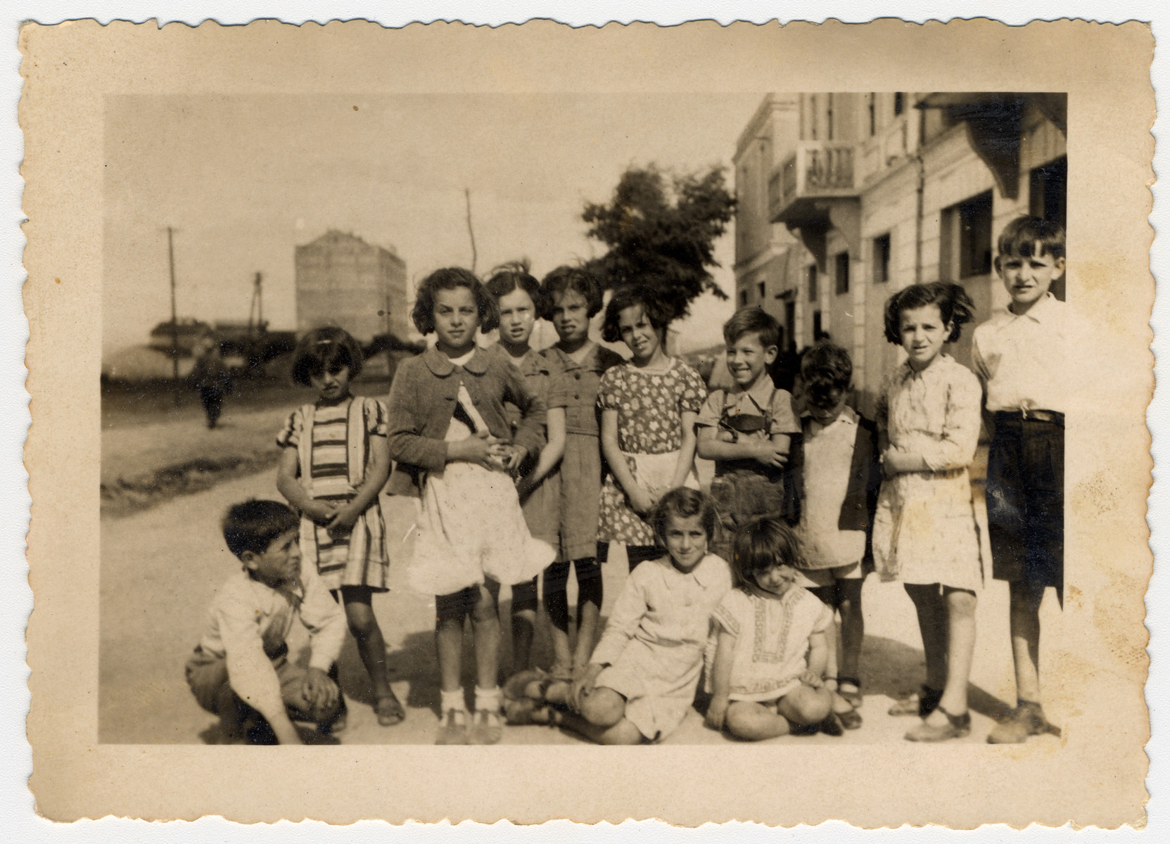 German and Austrian refugee children pose with Albanian children shortly after their arrival.  Johanna Gerechter is standing in the center with an apron.  Also pictured are Eva, Hannelore and Alex Meyer.
