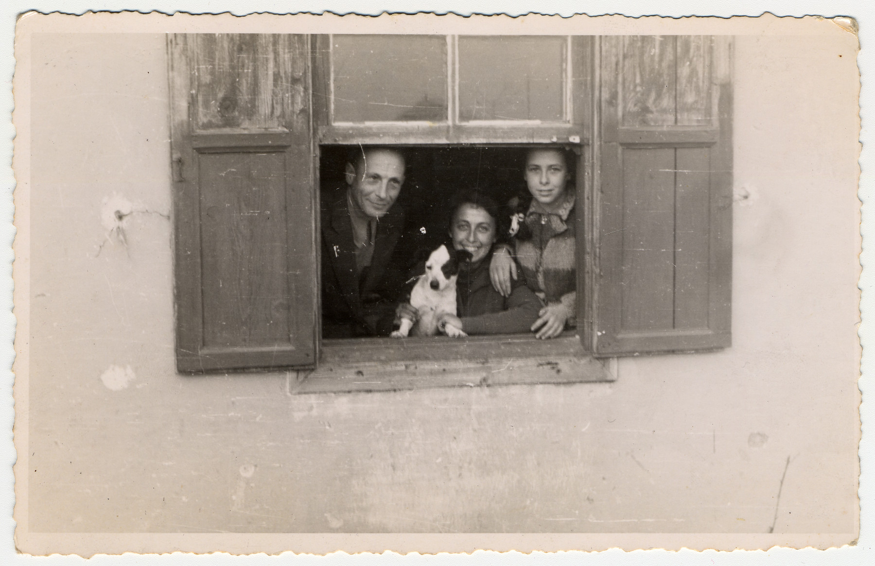 Jewish refugees look through the window of their one room home in Albania.  Pictured are Siegbert, Alice and Johanna Gerechter.