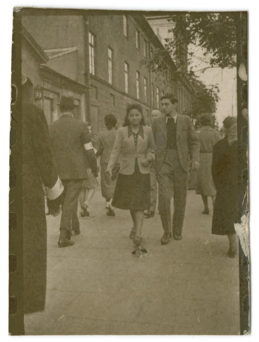 Miriam Wattenberg (Mary Berg) walks down a street arm in arm with her boyfriend Romek Kowalski.