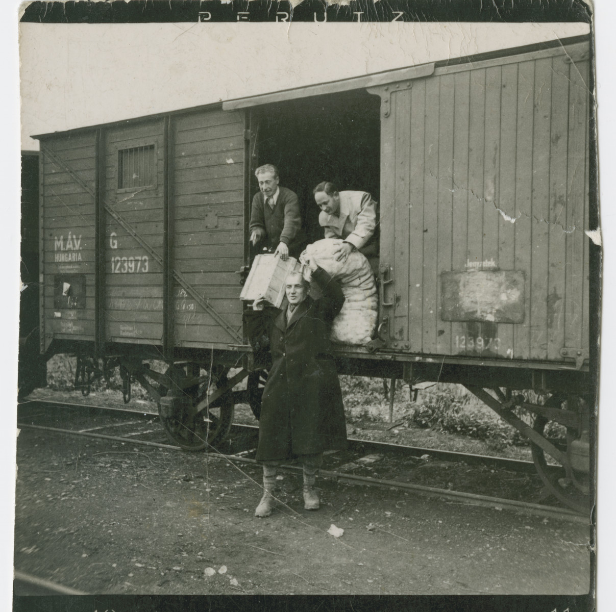 Hungarian Jews load or unload cargo into a cattle car while awaiting deportation to a forced labor battalion.  Among those pictured is Imre Winkler.