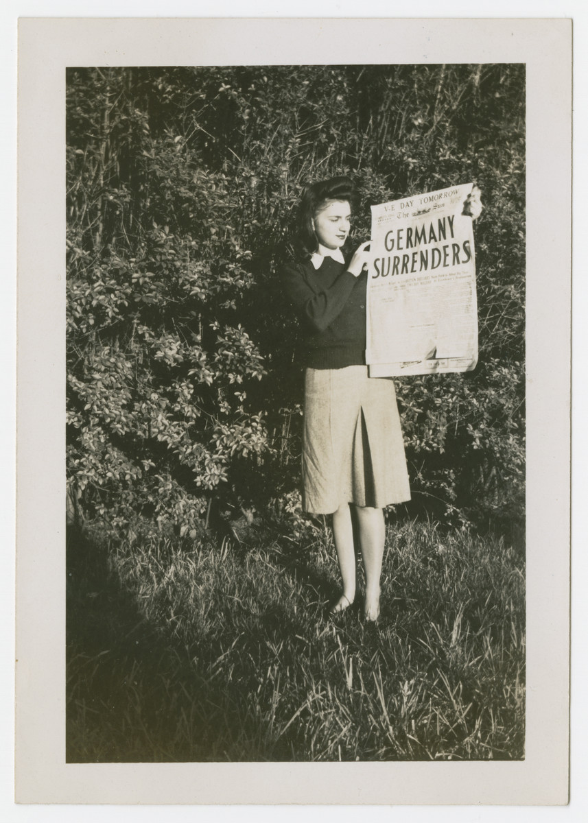 Mary Berg holds up a newspaper announcing the surrender of Germany.