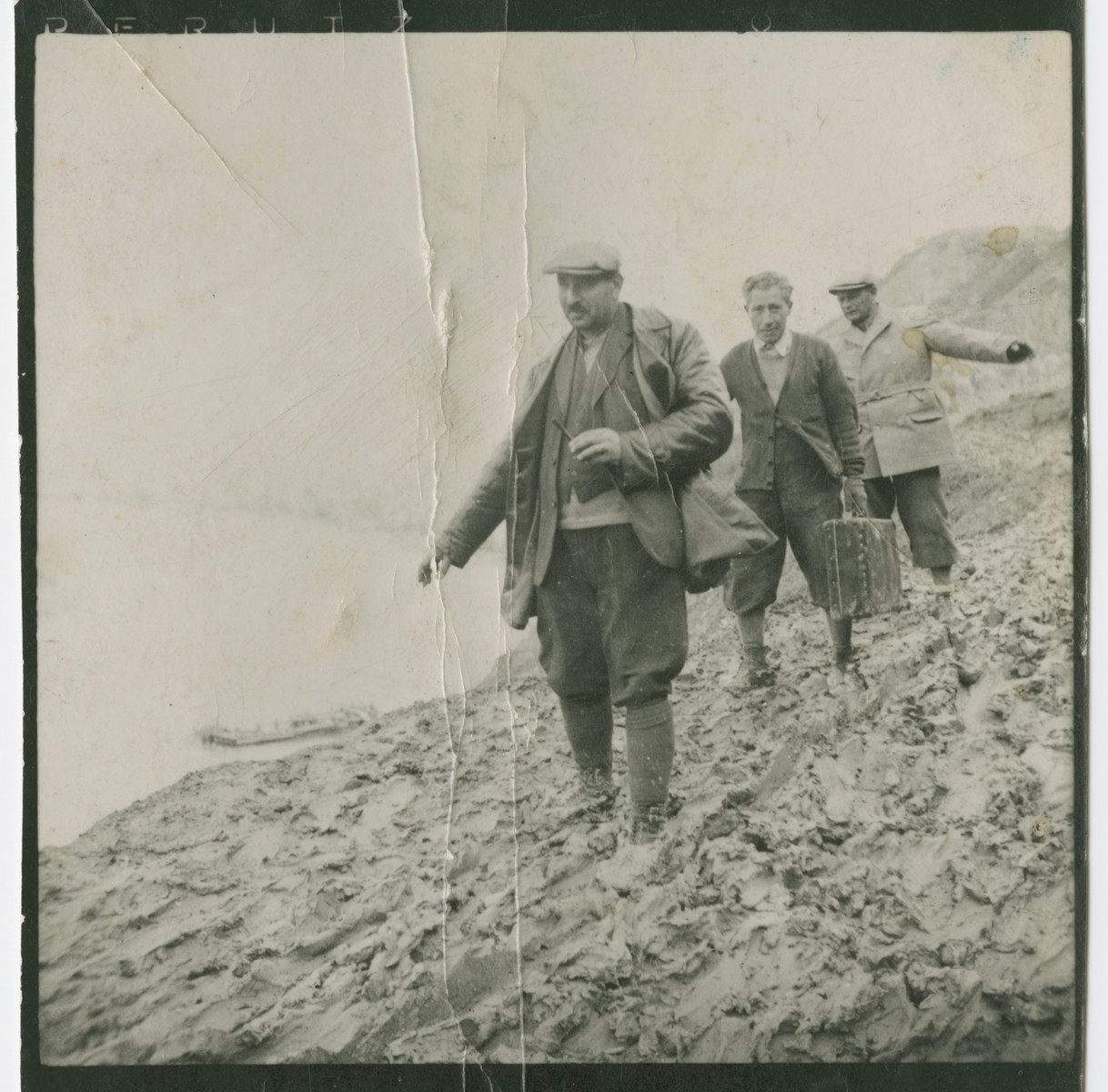 Three Hungarian Jews in a forced labor battalion walk down a hill.  Among those pictured is Imre Winkler.