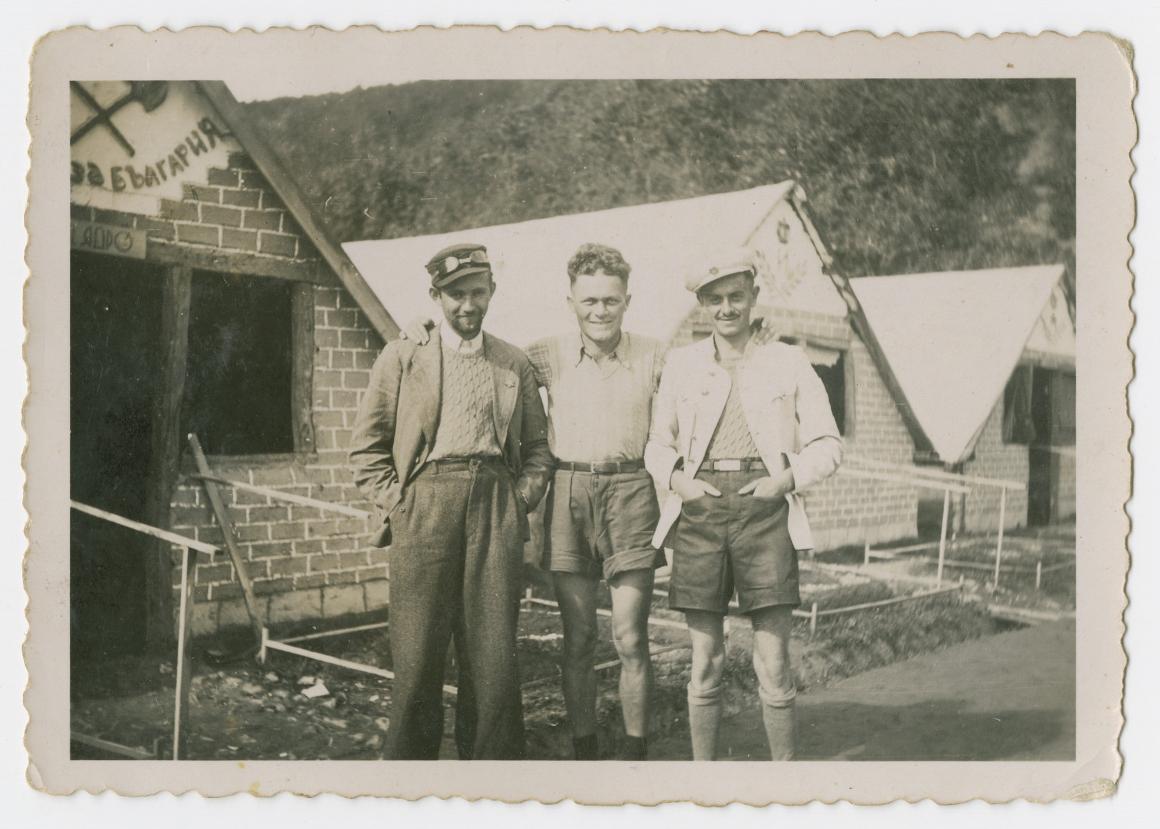 Portrait of three men in a Bulgarian labor camp standing outside a brick barrack.