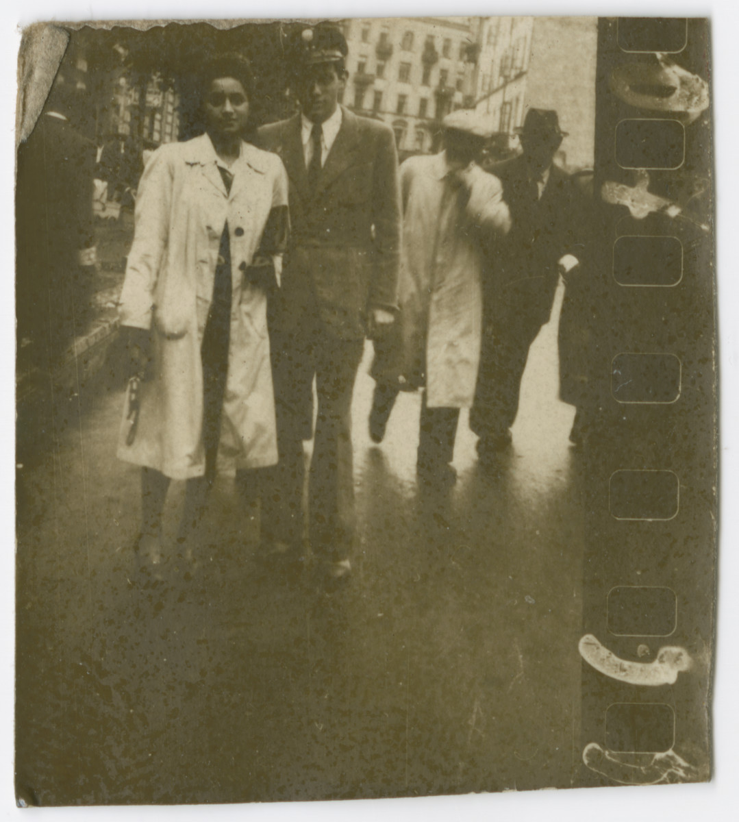 Miriam Wattenberg (Mary Berg) walks down a street of the Warsaw ghetto with a friend in the Jewish police.