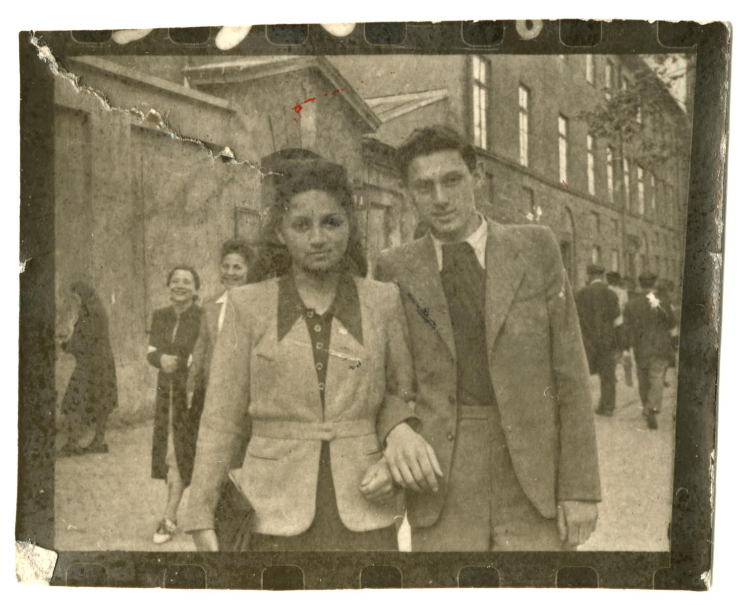 Miriam Wattenberg walks down a street in the Warsaw ghetto arm in arm with her with boyfriend Romek Kowalski.