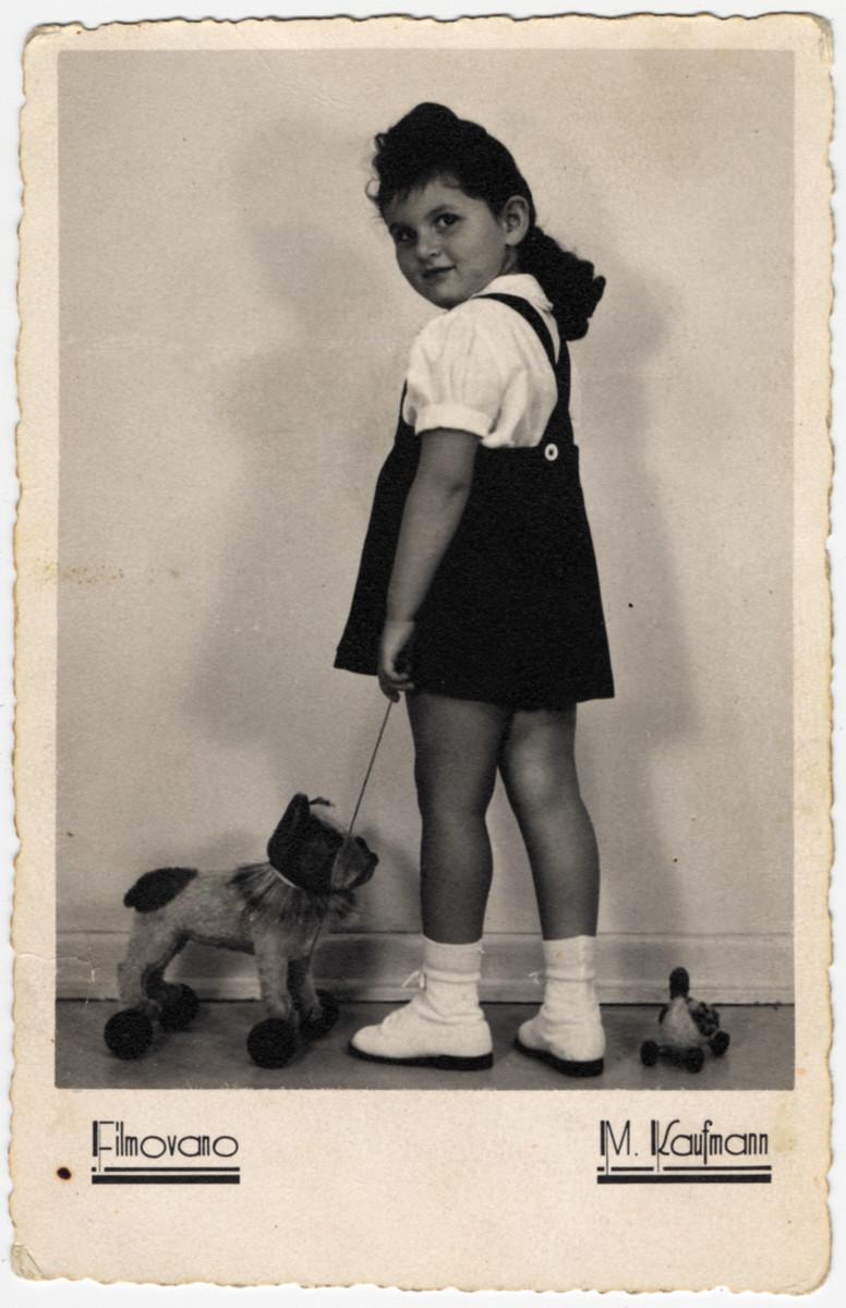 Studio portrait of Rina Elisha pulling a toy dog on a string.