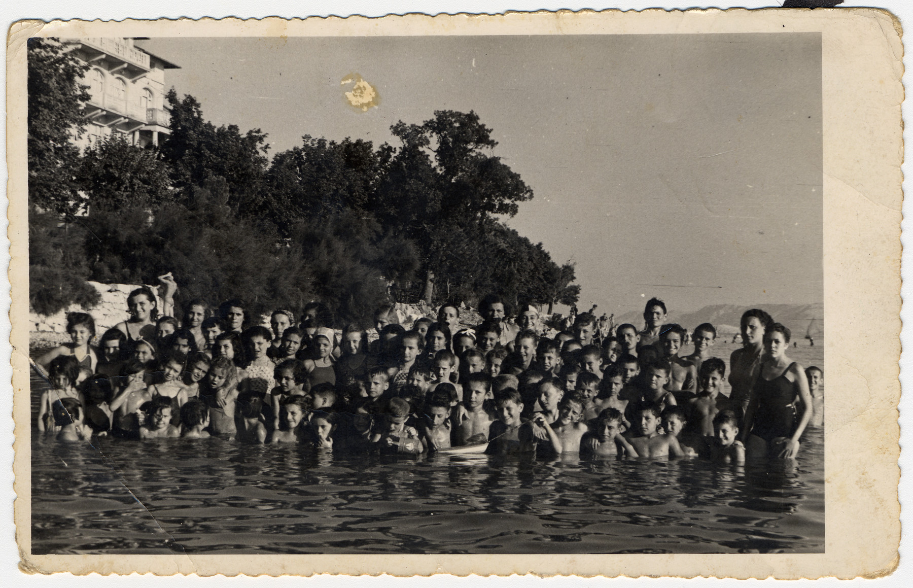 Children in a postwar Jewish summer camp pose for a group portrait in either a lake or the sea.