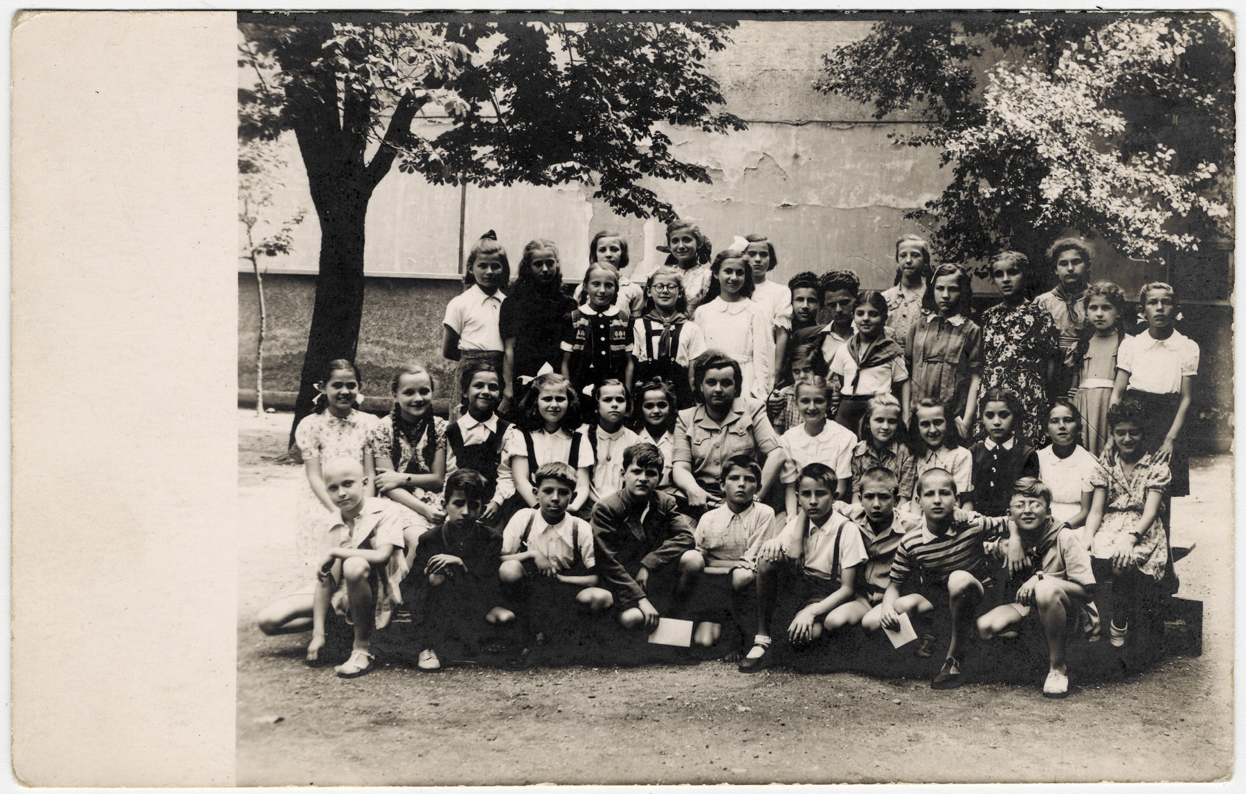 Postwar picture of an elementary school class in Zagreb.  Many of the students are wearing red Pioneer neck scarves.  Among those pictured is Rina Willer, standing third from the right.