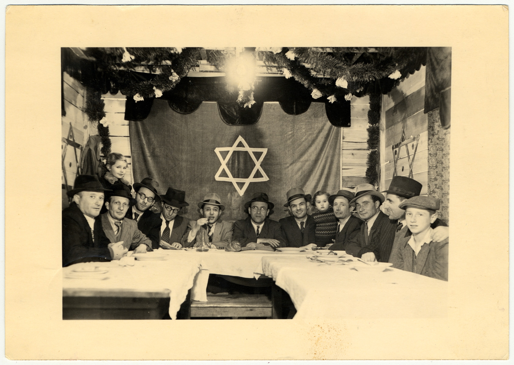 Jewish men gather in a communal sukka in the Amberg displaced person's camp.  On the left is Mordka Malach, the father of the donor. Rabbi Zanger is in the center and the head of the community is to his right.