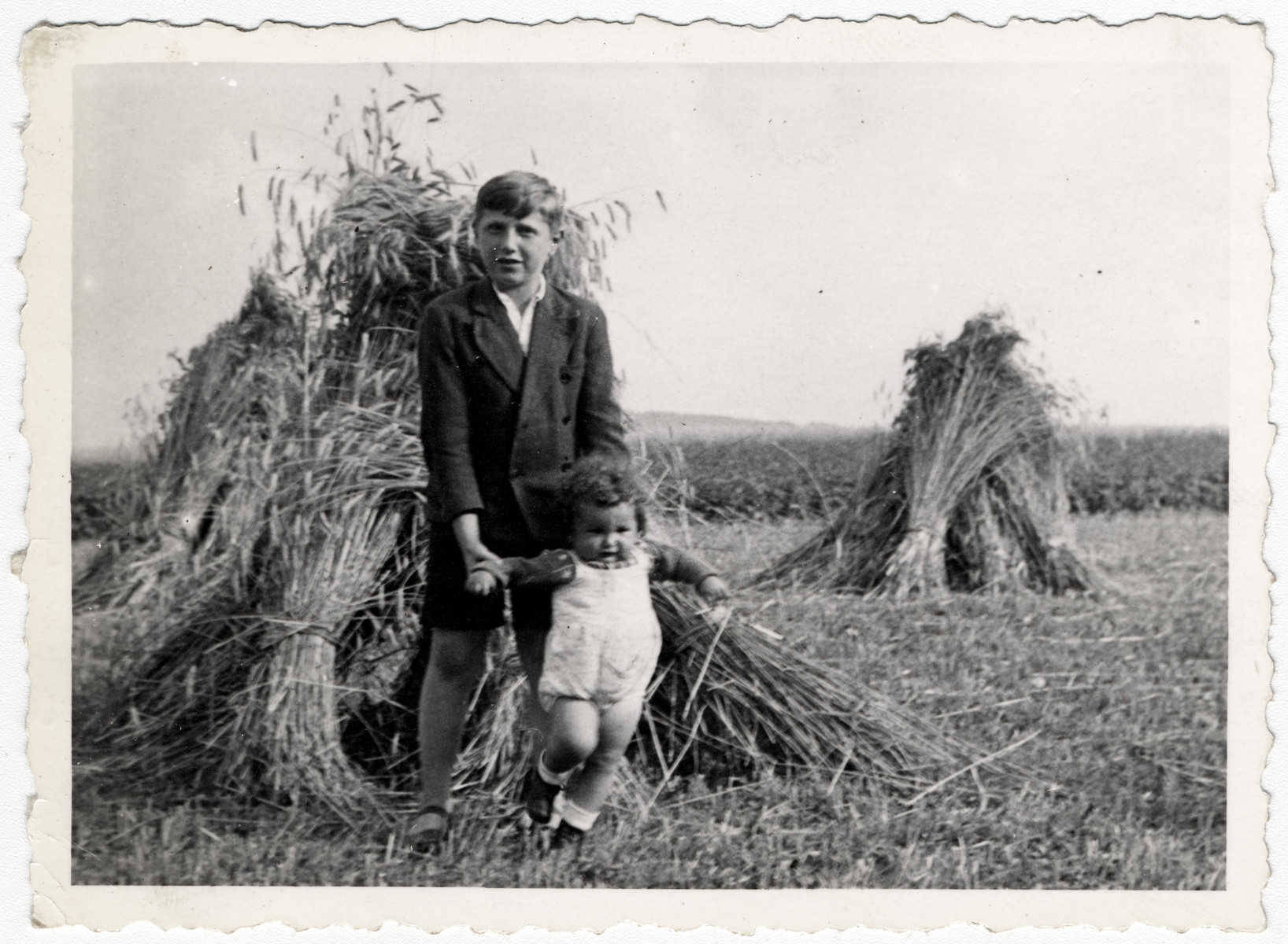 Abraham Malach poses with his baby cousin Abraham Reichman in front of a haystack near the Amberg displaced persons' camp.