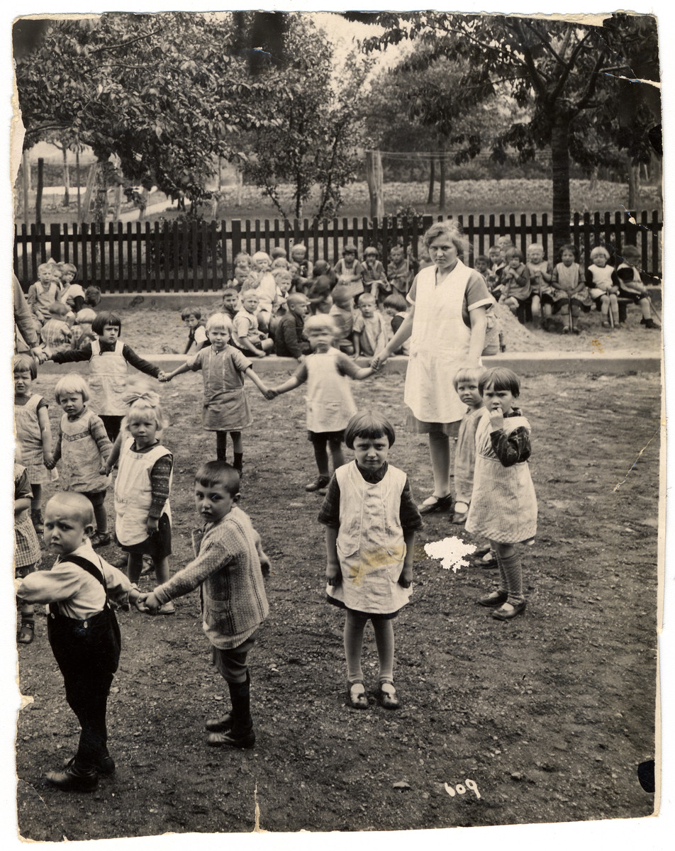 Children in a kindergarden in Gladbelk, Germany hold hands in the school playground.  Sol Bleisweis is pictured second from left , lower row.
