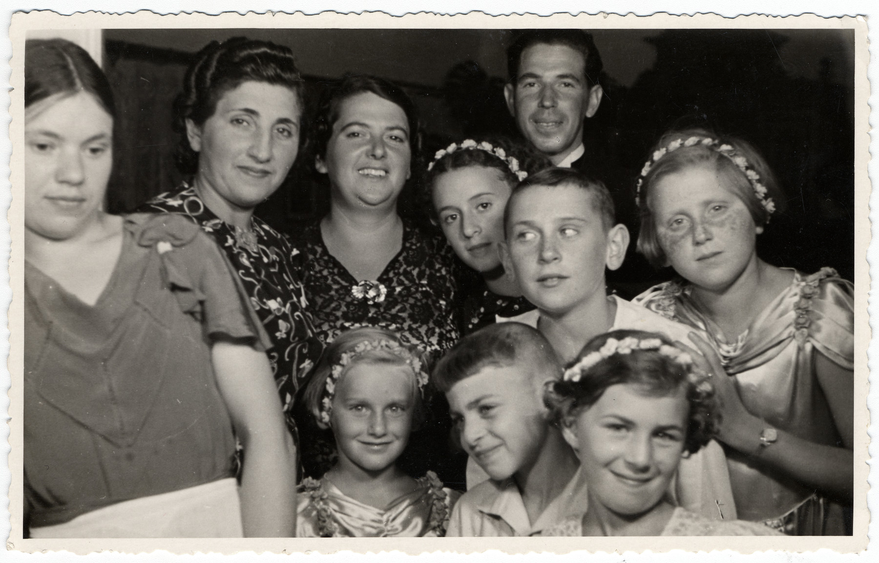 Group portrait of Latvian Jews photographed during a wedding celebration.  Lia and Bella Levenstein (far left) pose in matching dresses among relatives and friends during the wedding of David Levenstein and Hanna Thalberg in Ventspils, Latvia.  Frieda Lewenstein, Libin and Bella's mother (2nd from right), is also pictured. Neither Frieda nor her daughters survived the Holocaust.