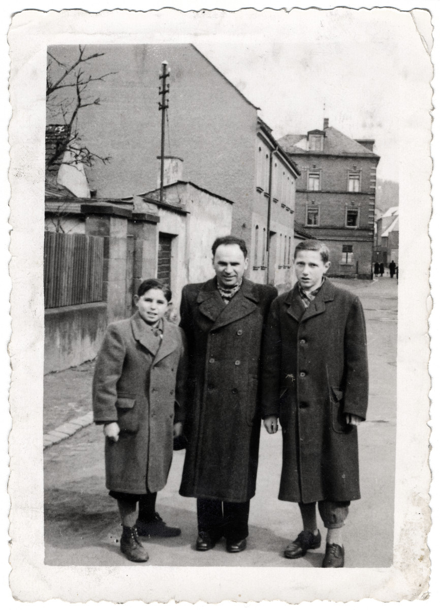 Abraham Malach poses on a street with Charles Friedman and his father.
