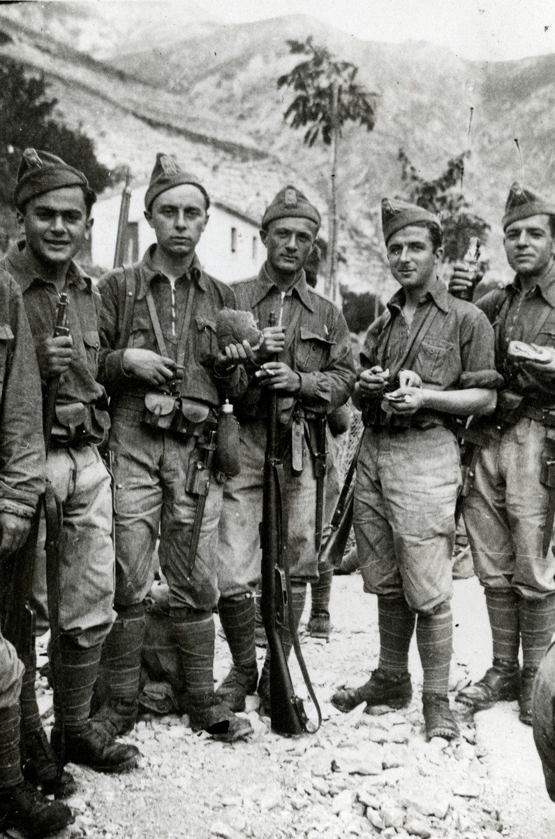 Five Italian soldiers pose with their weapons in a base near a mountain.  Pictured on the far left is Ugo Nizza.