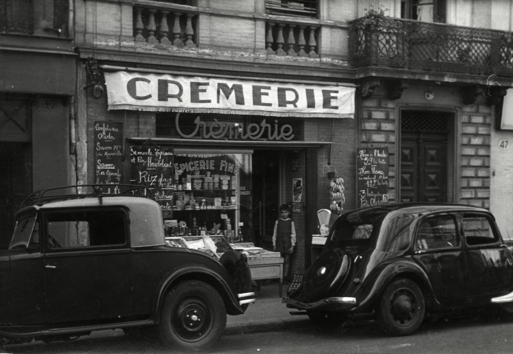 View of two automobiles parked outside the Cheraki's grocery store in Toulouse, France.