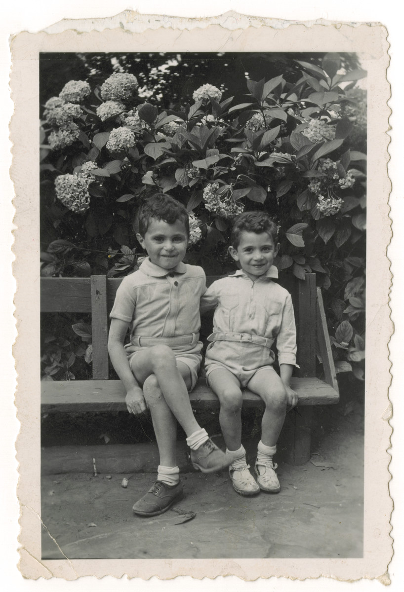 Two Jewish brothers who are living in hiding in German occupied Belgium, sit in the yard of the Mes Enfants children's home in Brussels.  Pictured are Nestor (right) and Jacques Hochglaube (left).