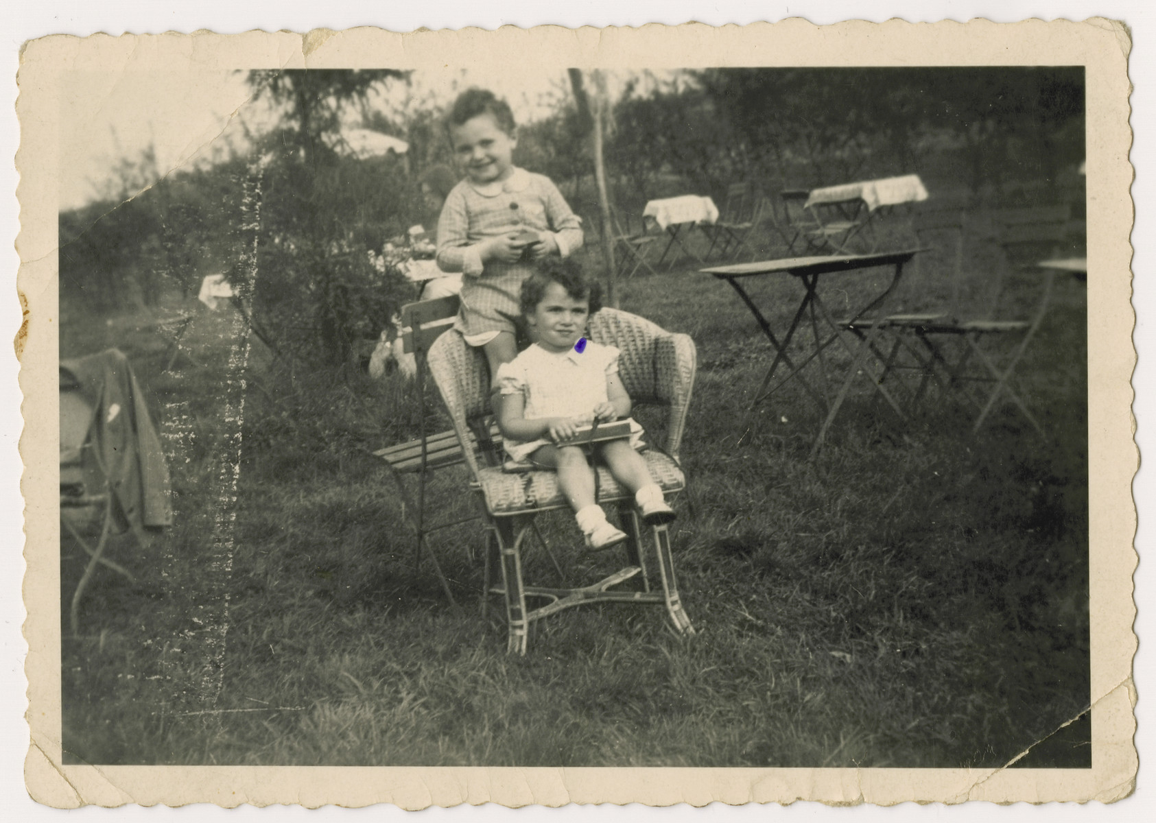 Two Jewish children placed in a children's home before  the invasion of Belgium, seen posing on a chair at a corner cafe dring their mother's weekend visit.    Pictured are Nestor and Jacques Hochglaube.