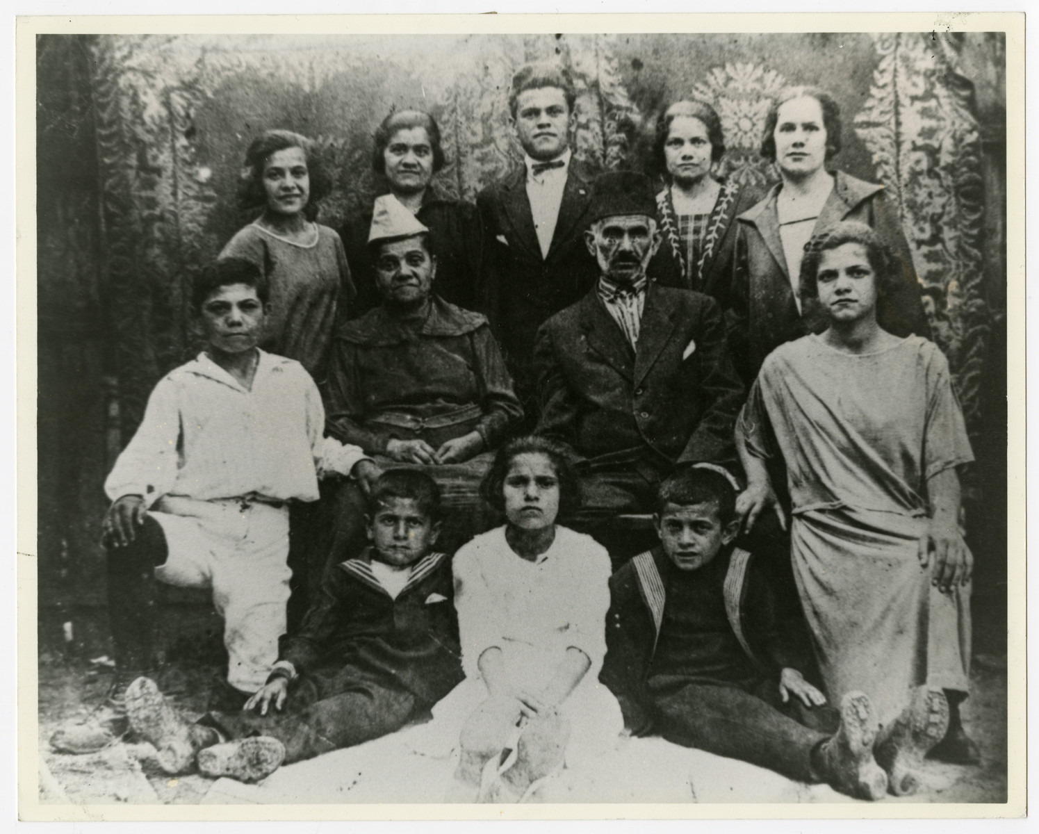 Group portrait of the Levi family in Banja Luka, Yugoslavia.   Moses and Rachel Levi are seated in the middle, surrounded by their ten children. David, in the white shirt, is next to his mother. The youngest son, Josef, is seated on the left.