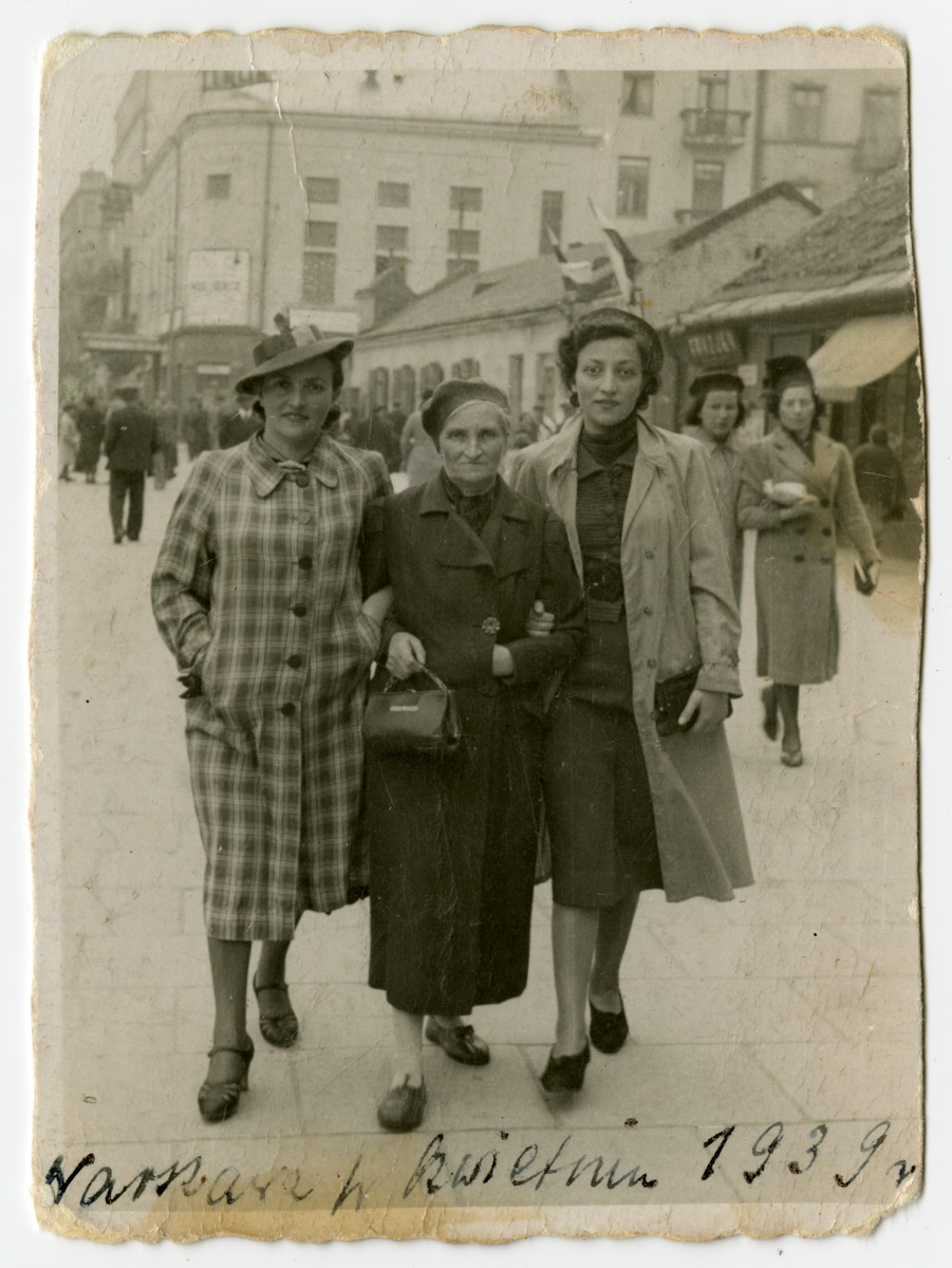 Chana Szwarcberg Kupersztajn (middle) walks down the street with her two daughters: Hinda Biberman on the left and Klara on the right.