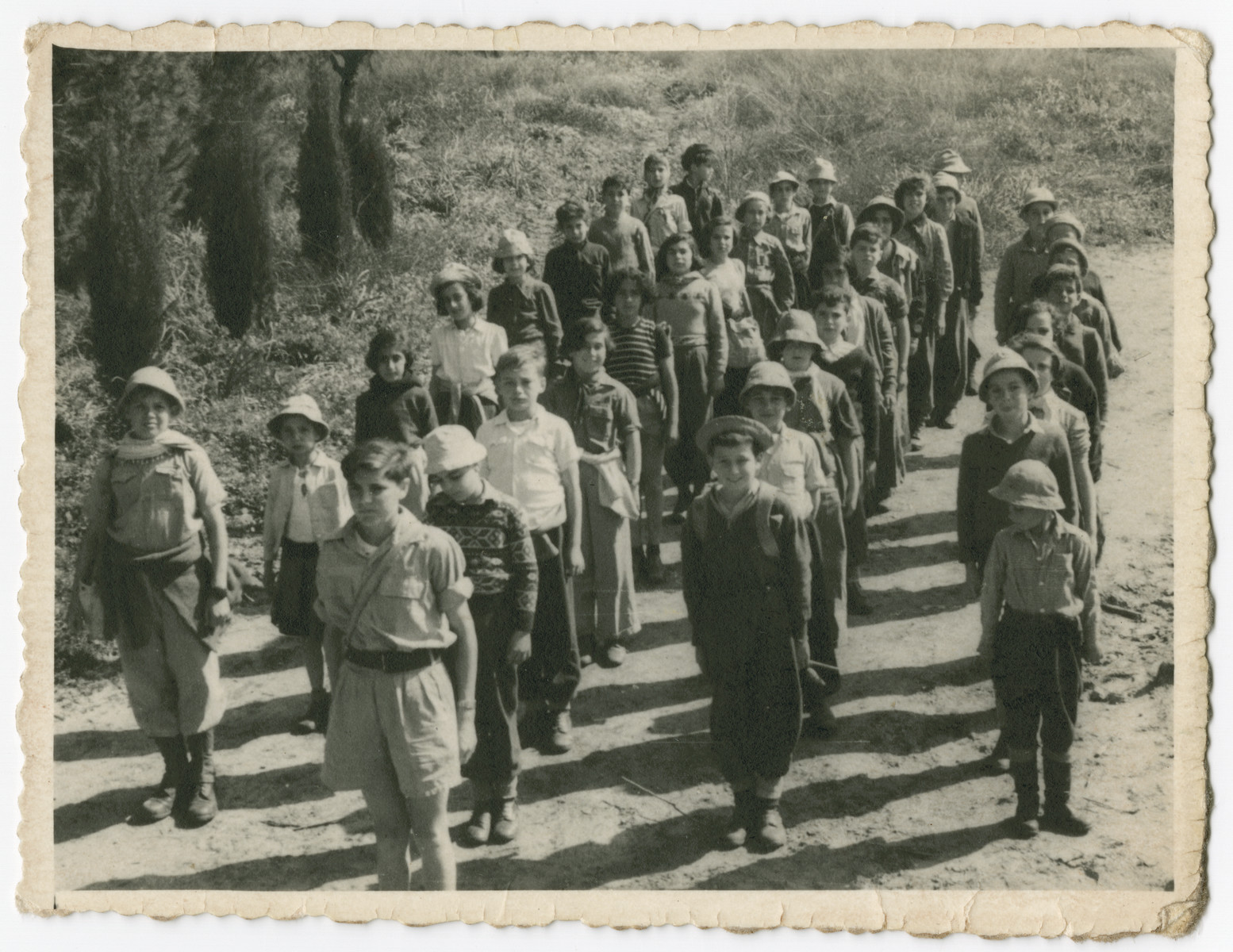 Nestor Hochglaube stands in formation with a group of children at the Hadassim youth village in Israel.  He is pictured in the fourth row, second from the right.