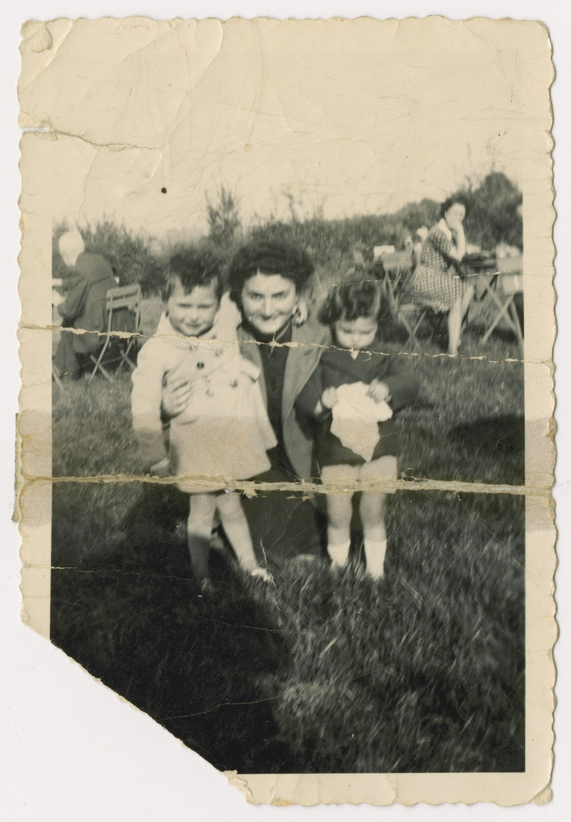 Two Jewish children placed in a children's home before  the invasion of Belgium, seen posing on a chair at a corner cafe dring their mother's weekend visit.    Pictured are Nestor and Jacques Hochglaube and their mother, Frymetta Hochglaube.