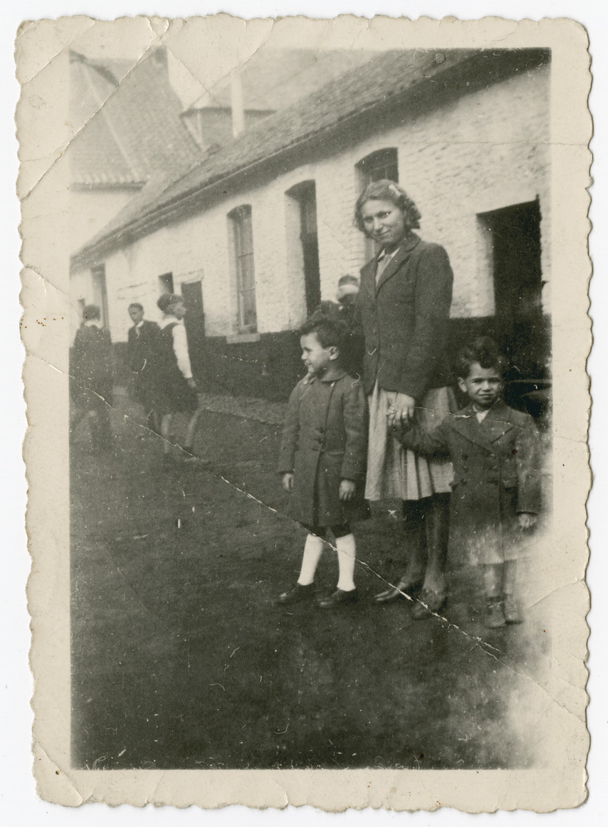 Two Jewish brothers stand on either side of the German maid who is hiding them on her farm in the Belgian countryside.    Pictured is Nestor Hochglaube (right) and his brother Jacques.