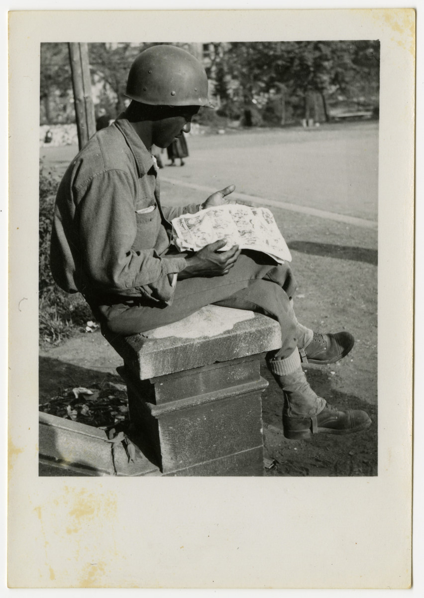 An African American soldier reads a newspaper in Pilsen, Czechoslovakia on its liberation day.