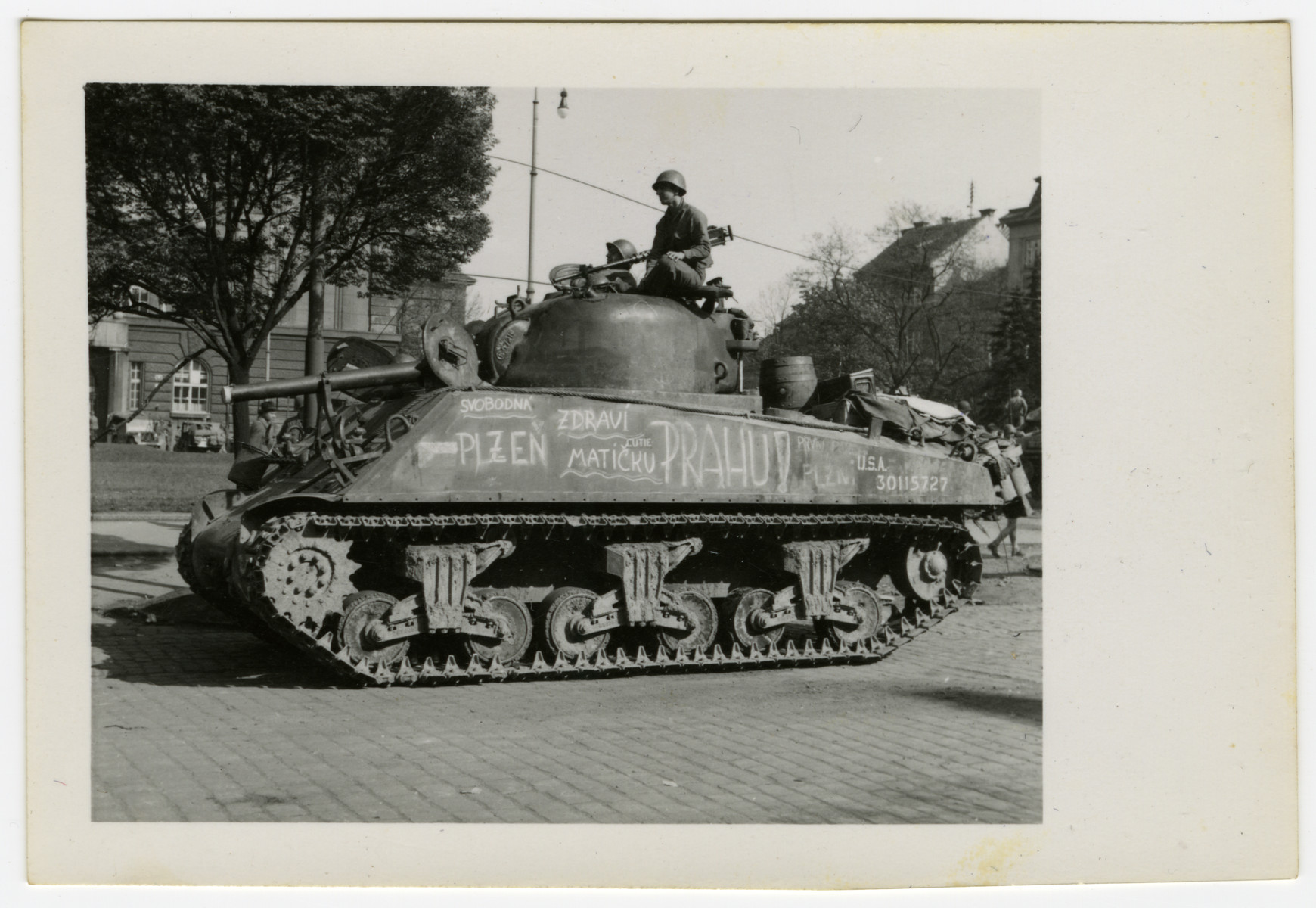 Am American tank drives down a street in Pilsen, Czechoslovakia on liberation day.