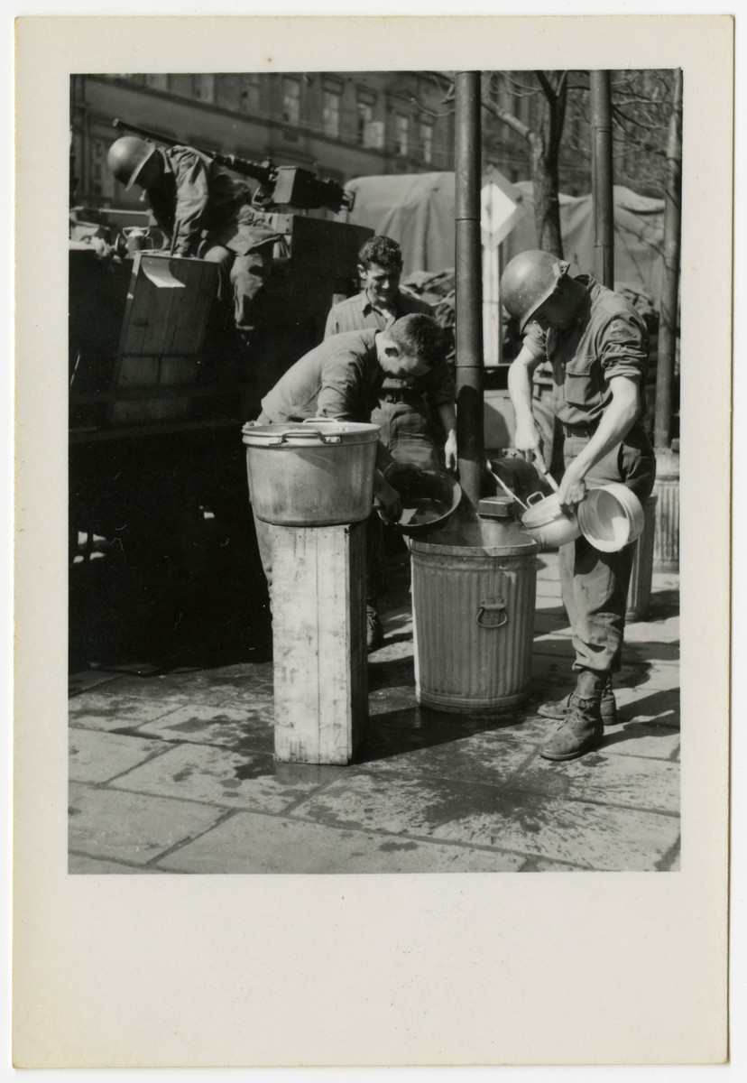 American soldiers scrape out pots on liberation day in Pilsen, Czechosovakia.