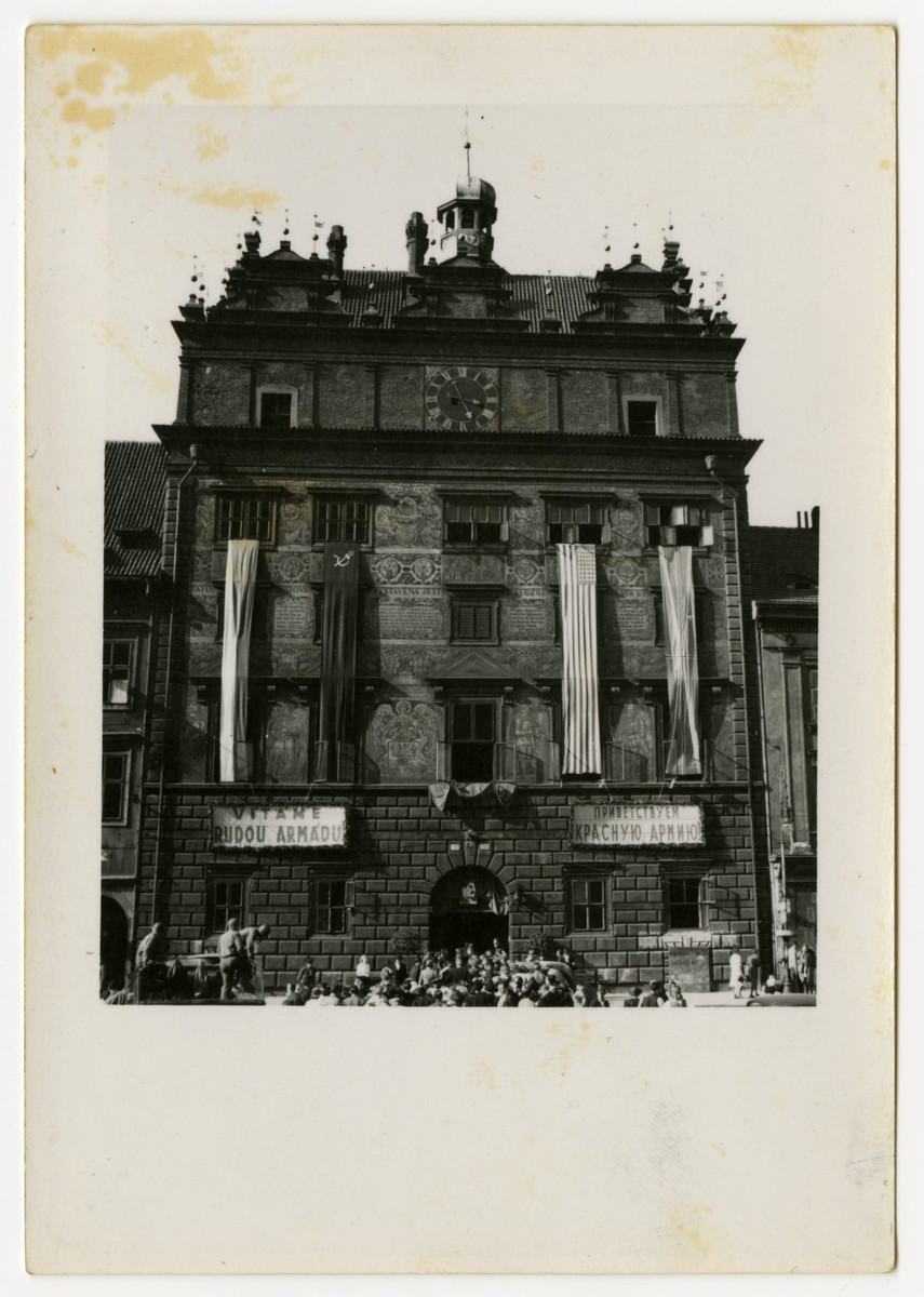 """People gather outside a large building in Pilsen, Czechoslovakia adorned with Czech, Soviet and American flags.  The sign on the left reads: """"Long live the Red Army."""""""