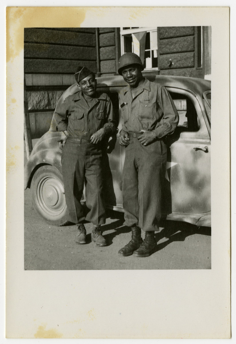 Two African American US soldiers pose in front of a car in Pilsen, Czechoslovakia on its liberation day.