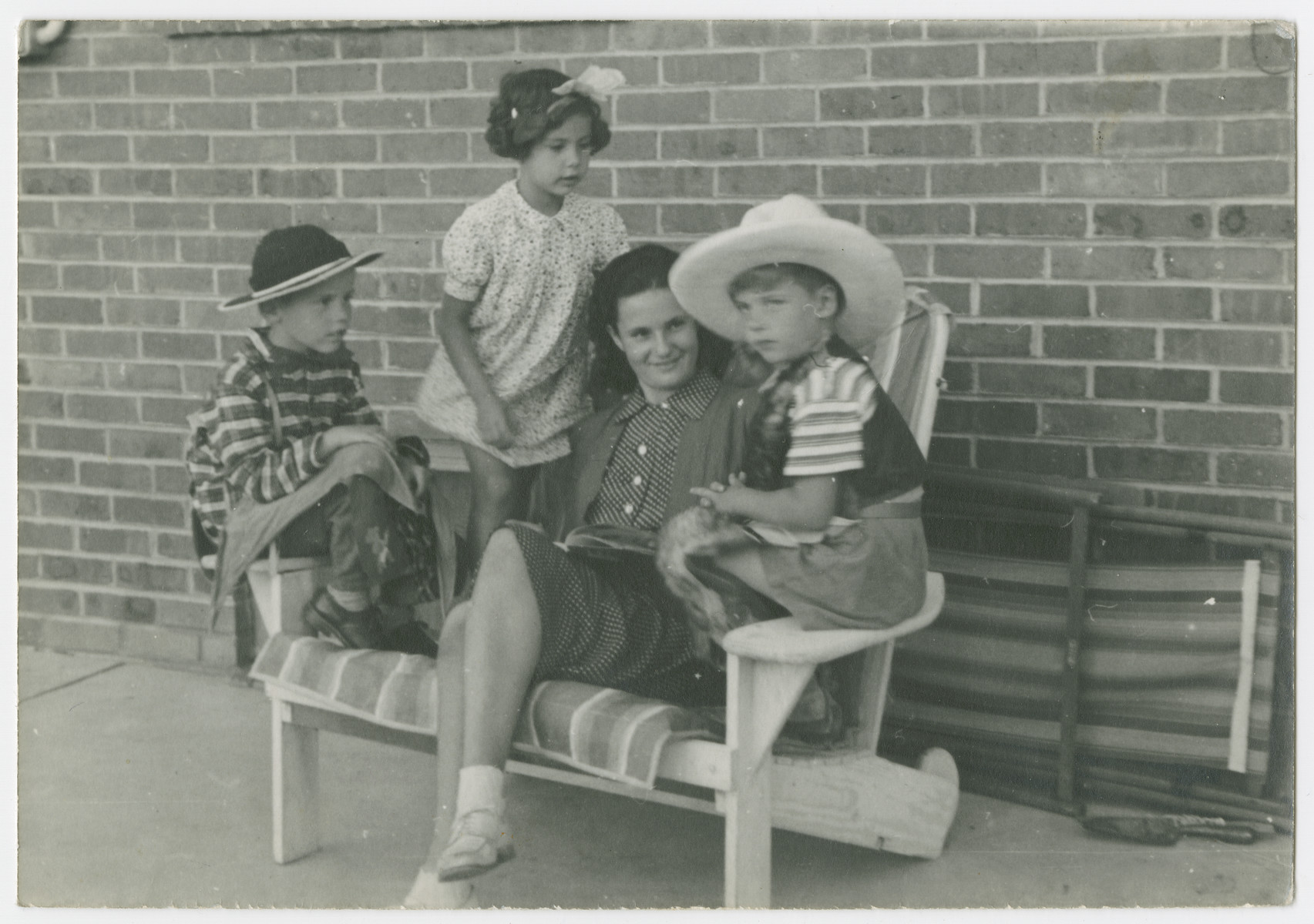 "Mara Vishniac sits on a bench surrounded by three younger children.  Ruth Rahn is to her left.  The Rahns and Vishniacs had been friends in Berlin and both immigrated to the United States to escape the Nazis.  The original caption reads: ""Mara and her kindergarten.  Ruth dressing ""girlishness"" (see bow in hair) probably to impress the fierce cowboys."""