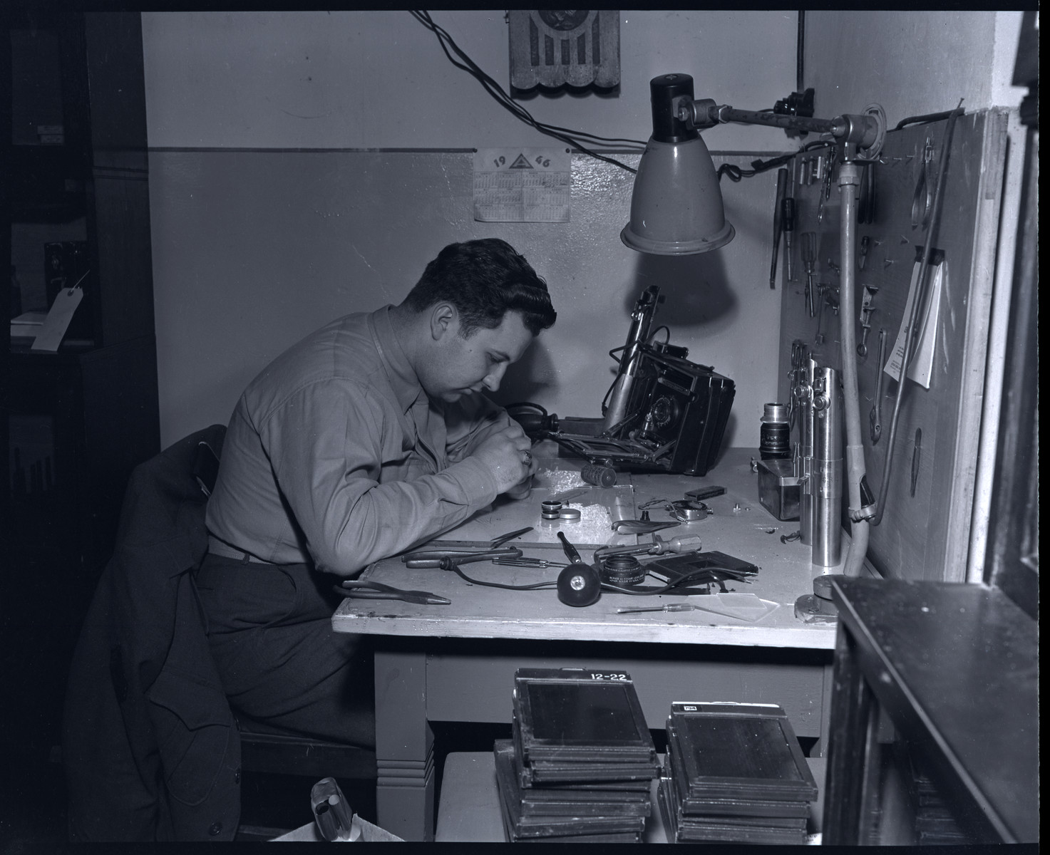 Herbert Lipman repairs cameras for Signal Corps photographers' use.